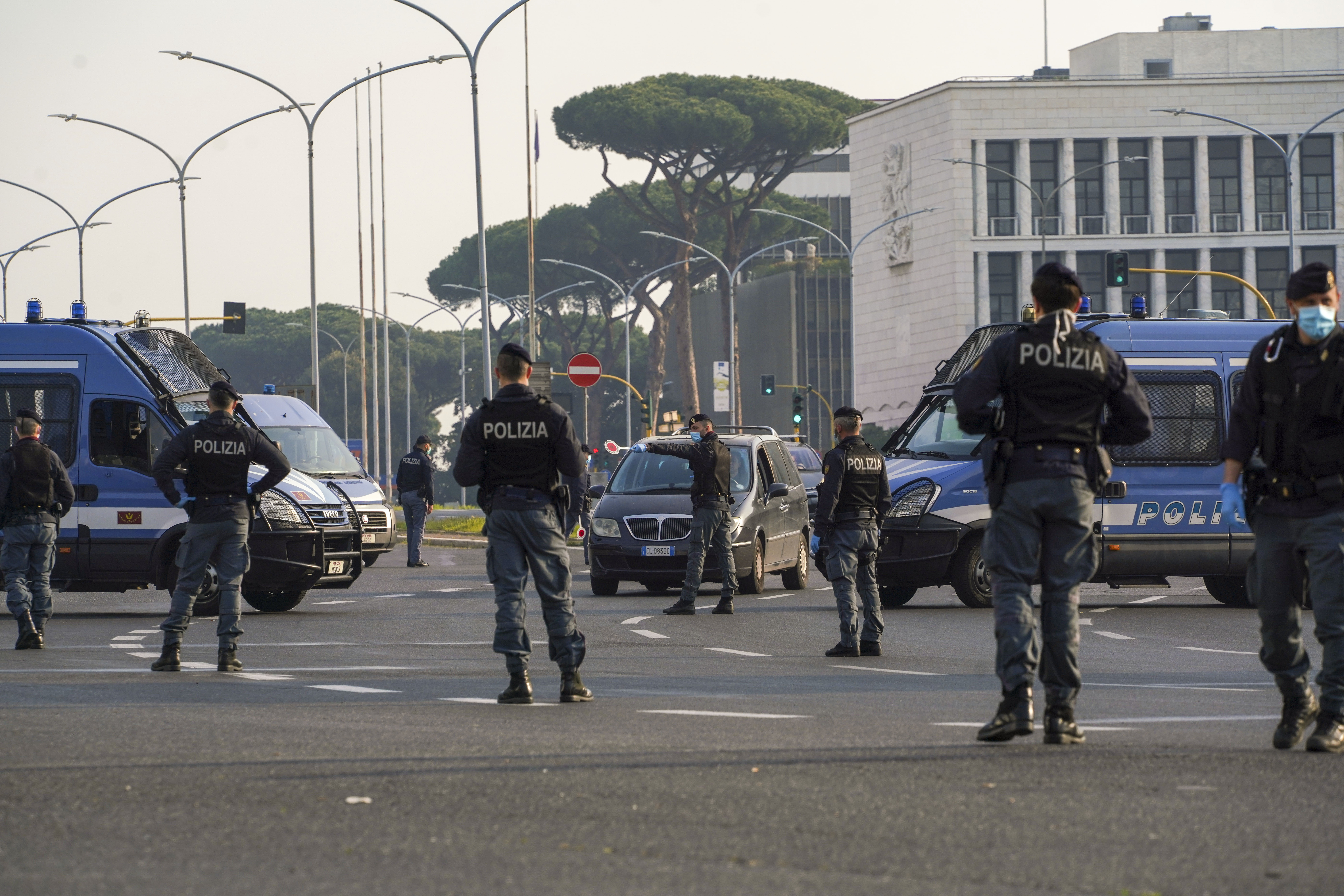 Police officers signal drivers to pull over at a road block in Rome on April 13.