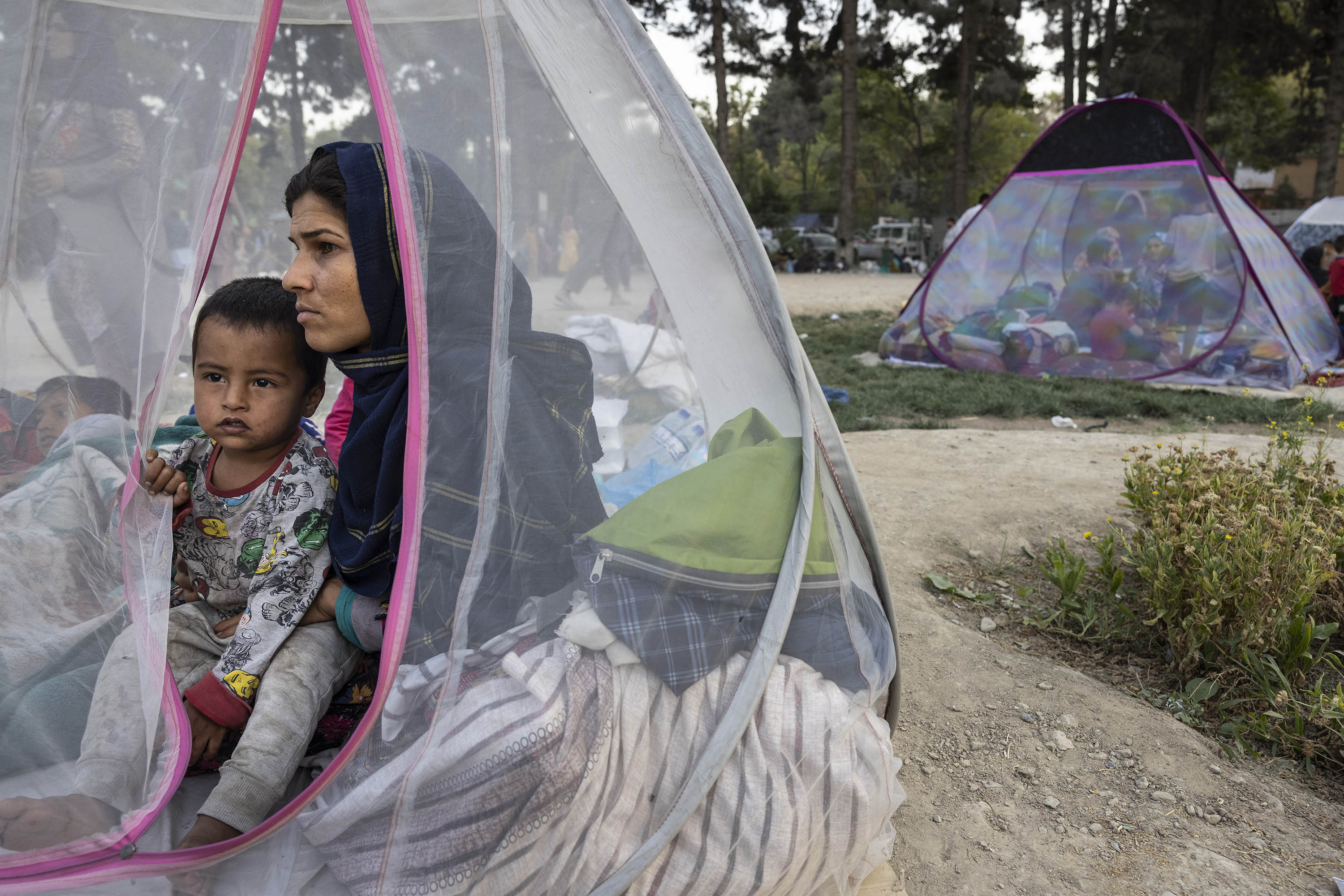 Displaced Afghans sit in a tent at a makeshift IDP camp at a park Kabul, Afghanistan, on August 12.