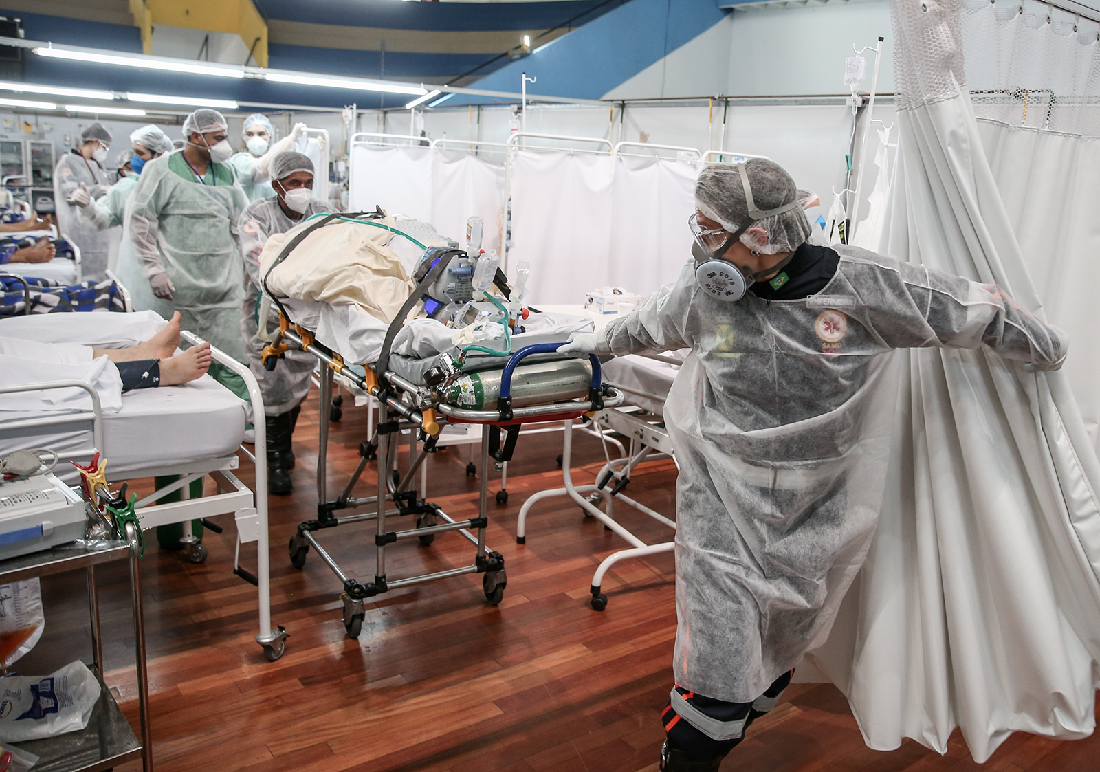 Medical staff members transport a patient on a stretcher at the Pedro DellAntonia Sports Complex field hospital in Santo Andre, Brazil, on March 11.