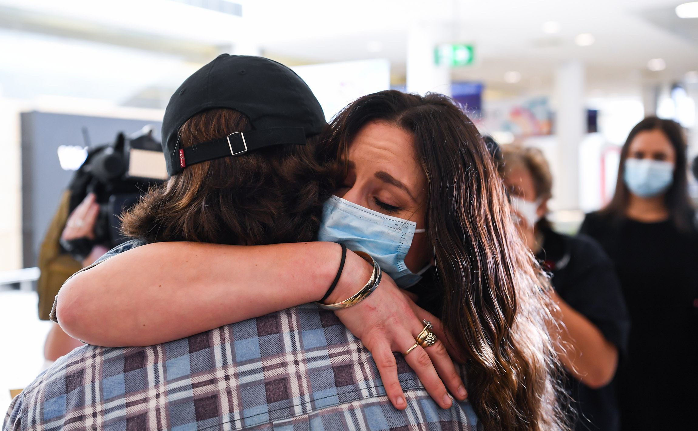 A woman hugs her loved one after arriving at Sydney's Kingsford Smith Airport on an Air New Zealand flight from Auckland on October 16.