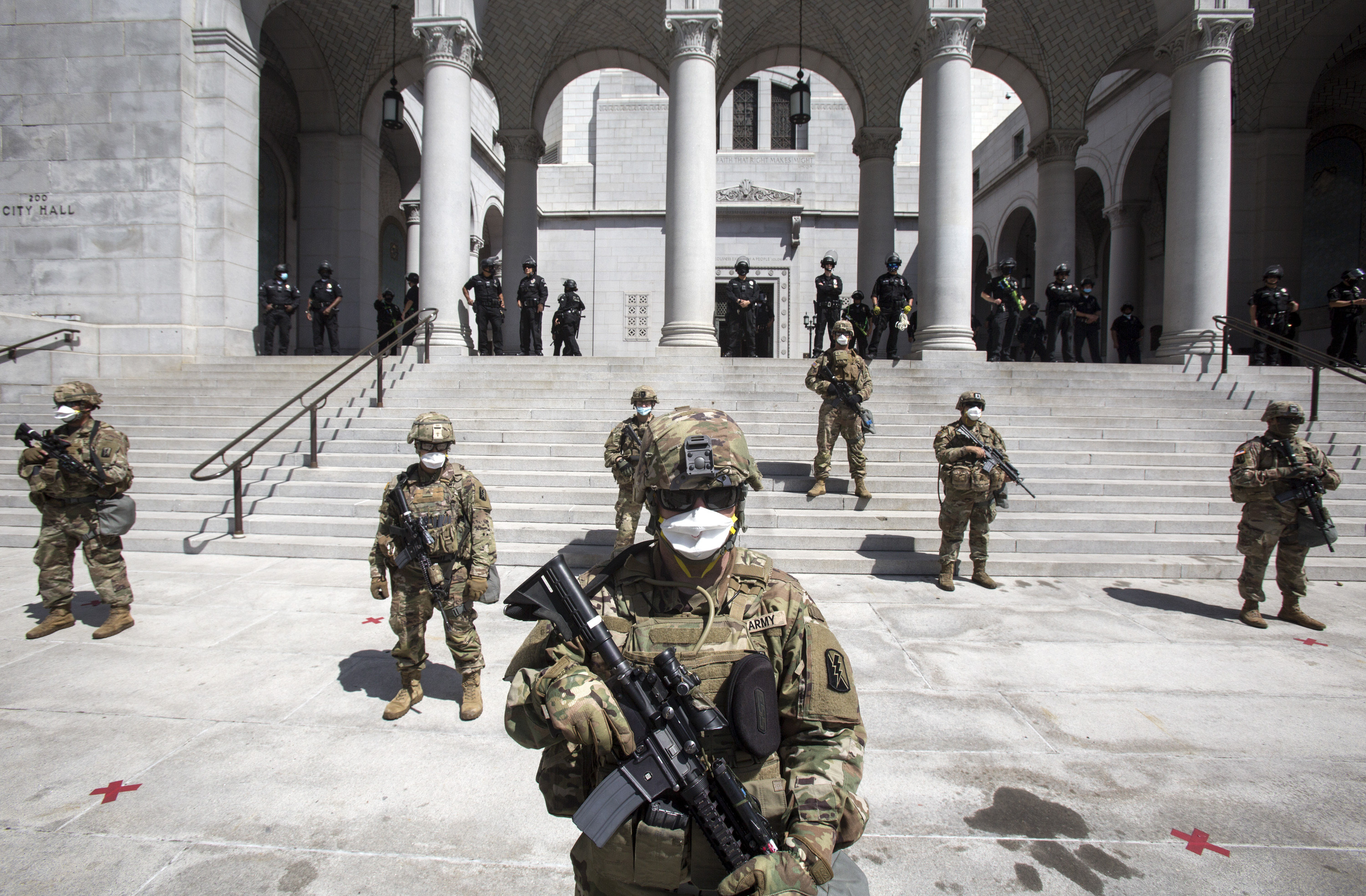 Members of California National Guard stand outside the City Hall, Sunday, May 31, in Los Angeles.