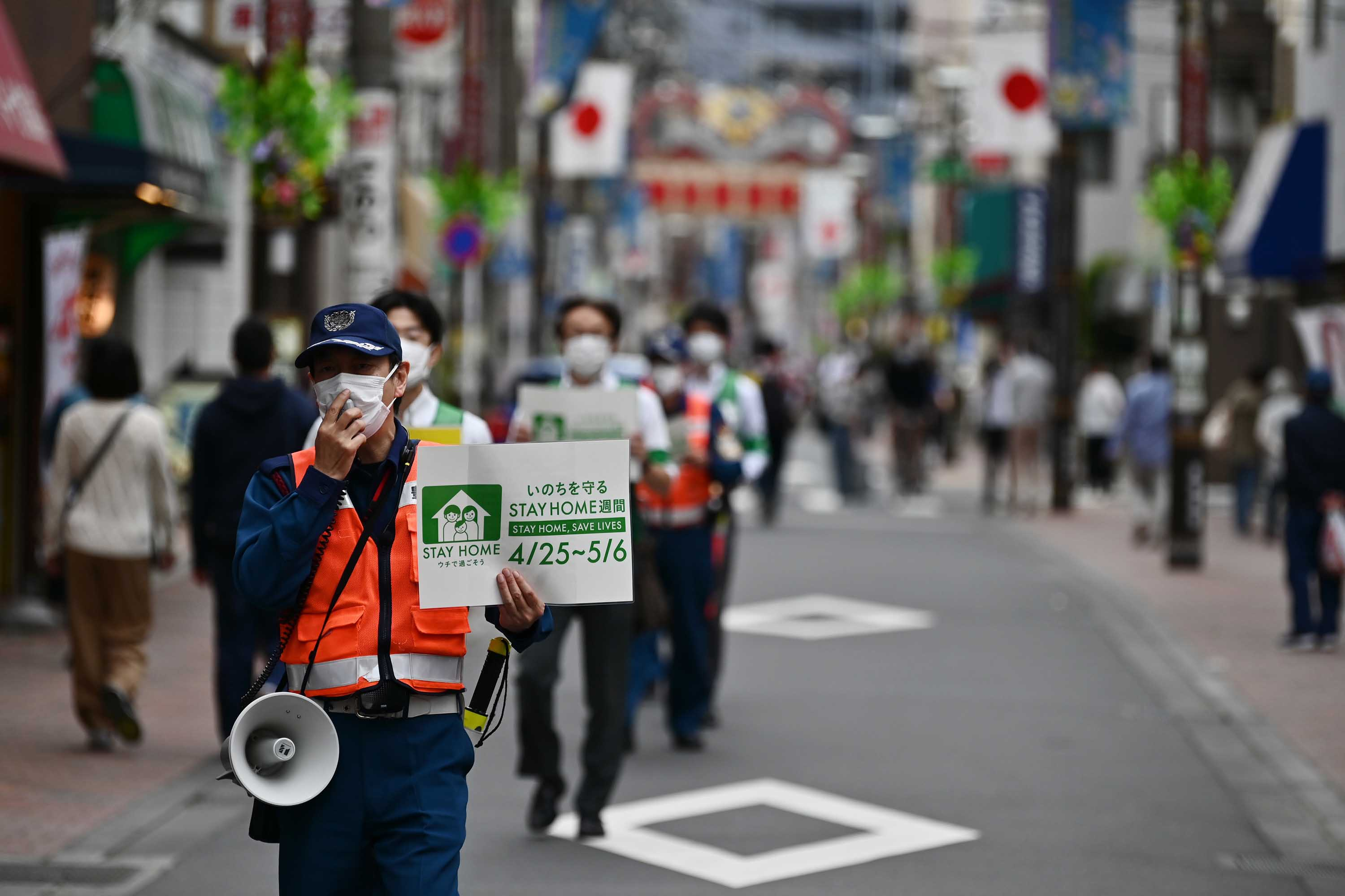 Municipal employees patrol a street asking people to stay home amid the coronavirus outbreak in Tokyo on May 4.