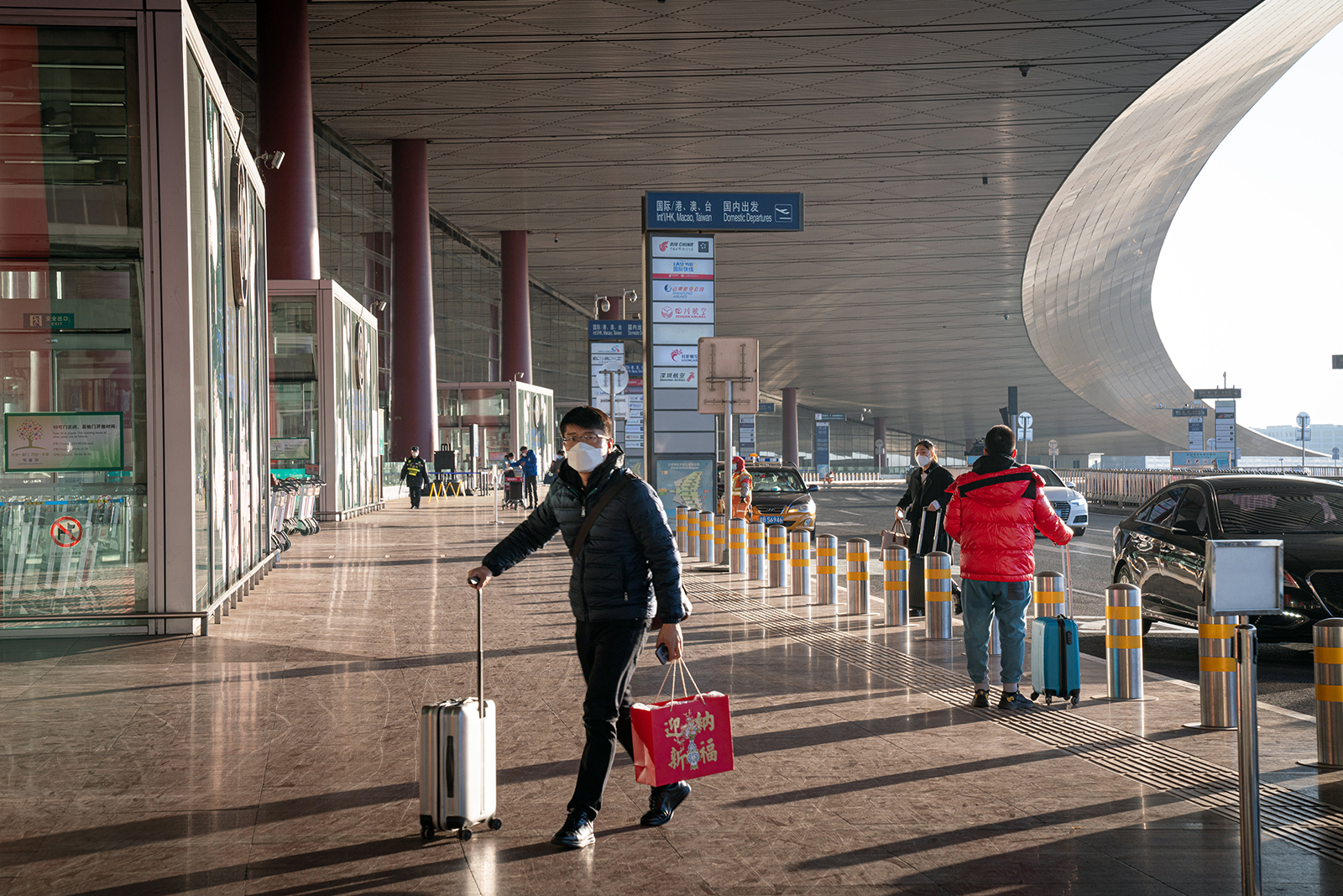 A traveler wearing a protective mask walks toward Beijing Capital International Airport ahead of the Lunar New Year in Beijing, on February 2.