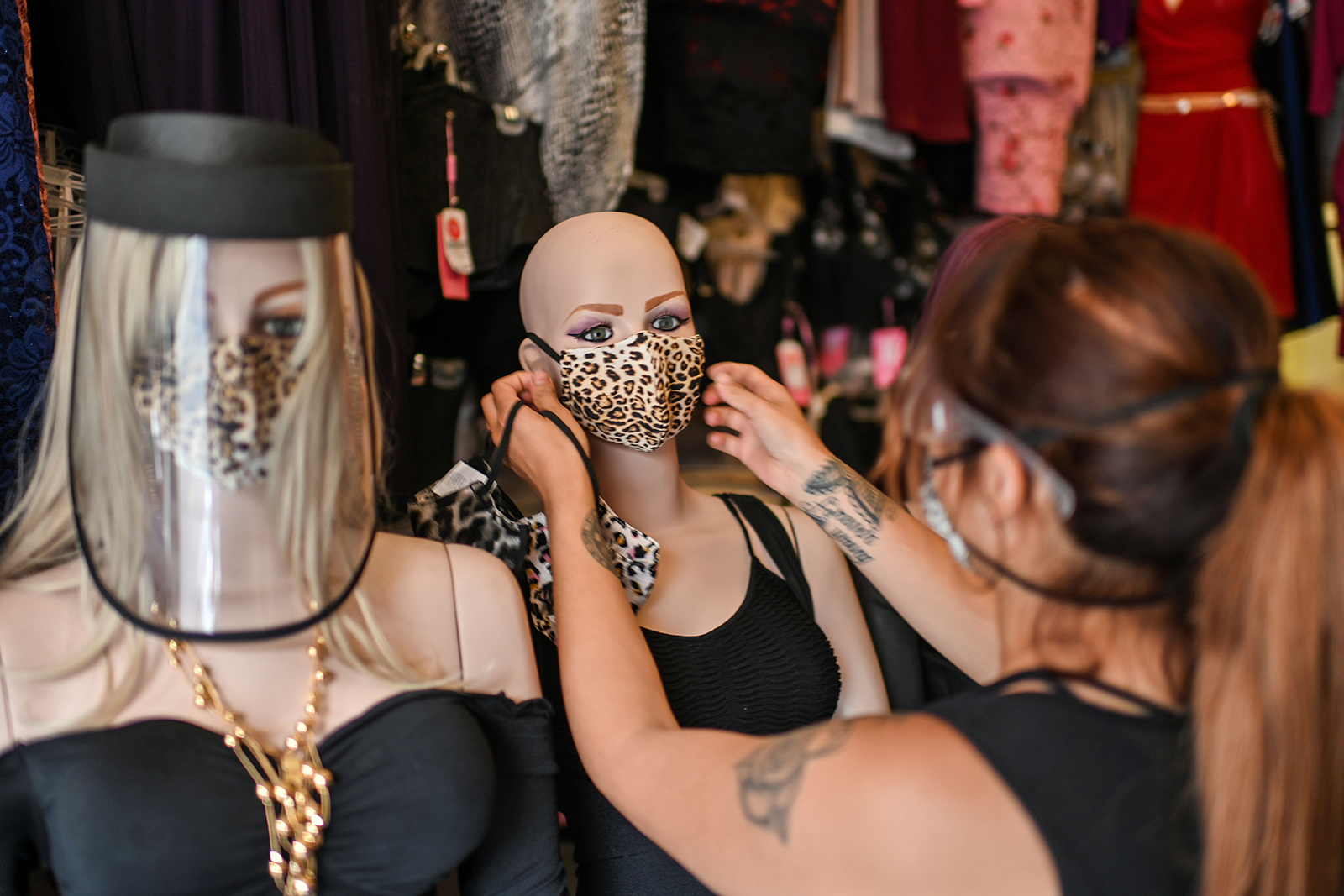 A woman puts a face mask on a mannequin while waiting for customers at her shop in Mexico City, on August 3.