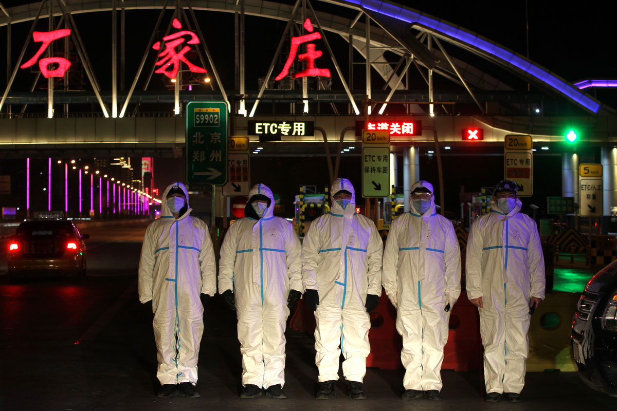 Police officers wearing protective suits stand guard at the entrance of an expressway on January 6 in Shijiazhuang, Hebei Province, China.