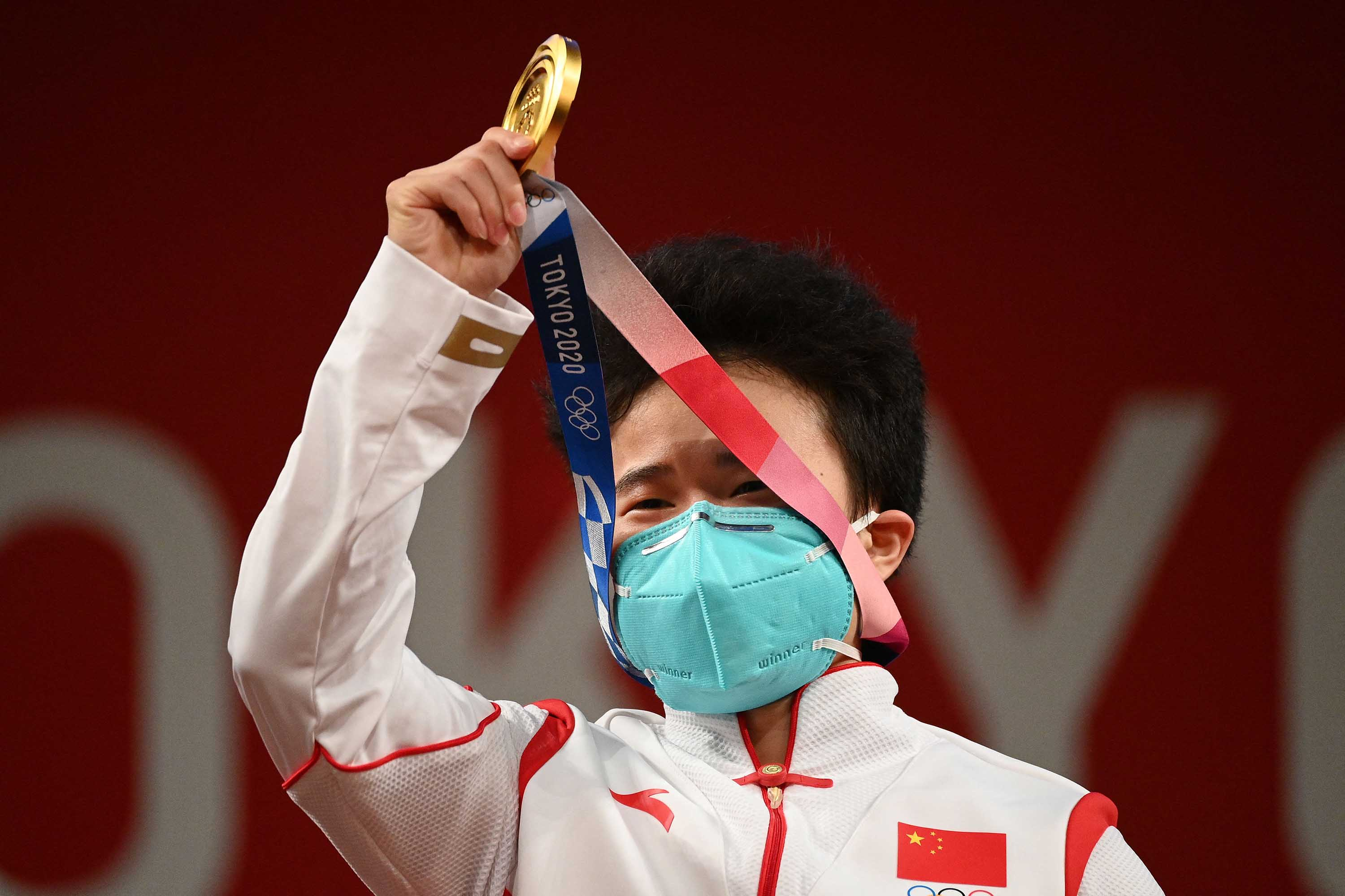 China's Hou Zhihui stands on the podium after winning Gold in the women's 49kg weightlifting competition on July 24.