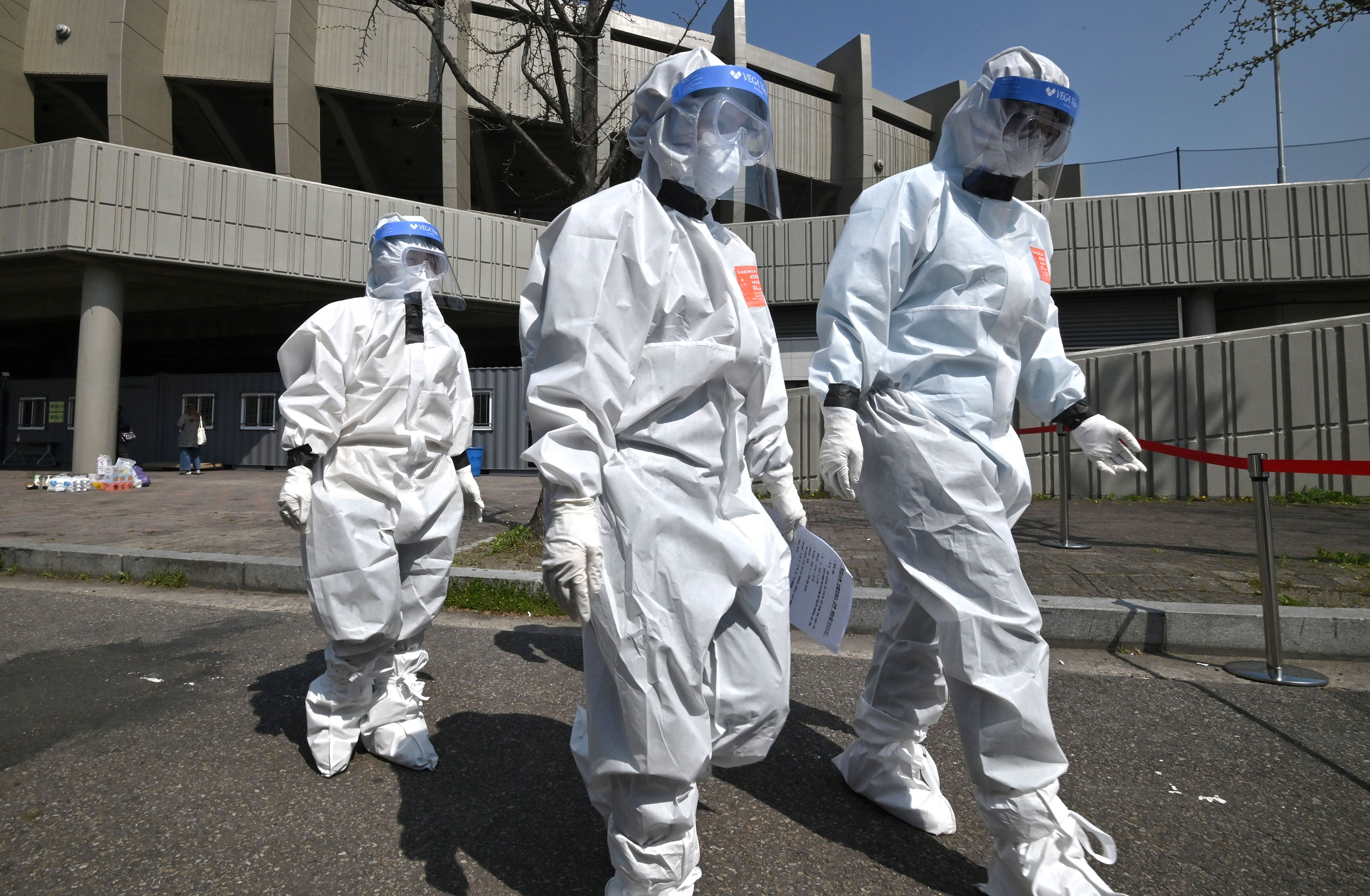 City officials wearing protective clothing arrive at a coronavirus testing station set up at Jamsil Sports Complex in Seoul on April 3.