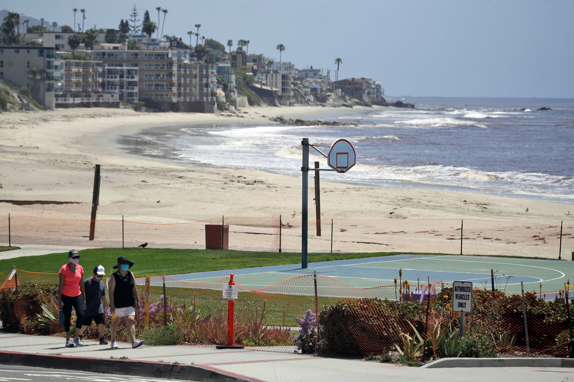 People walk past a closed off beach on May 3, in Laguna Beach, Calif.