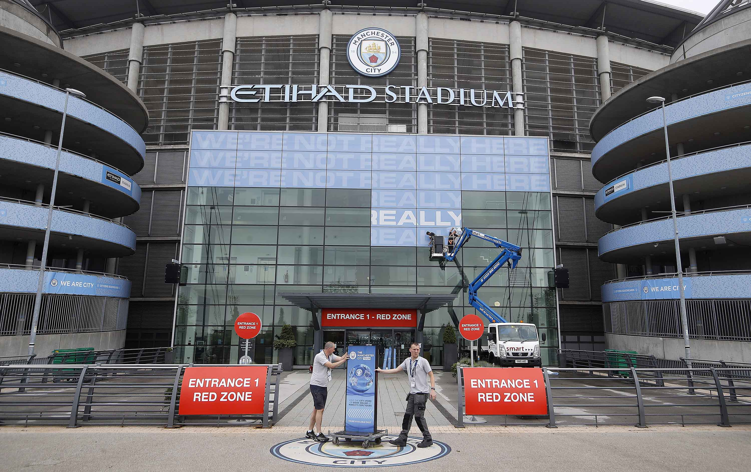 Workmen place signs outside the main entrance to the Etihad Stadium, home of Manchester City, on June 16.