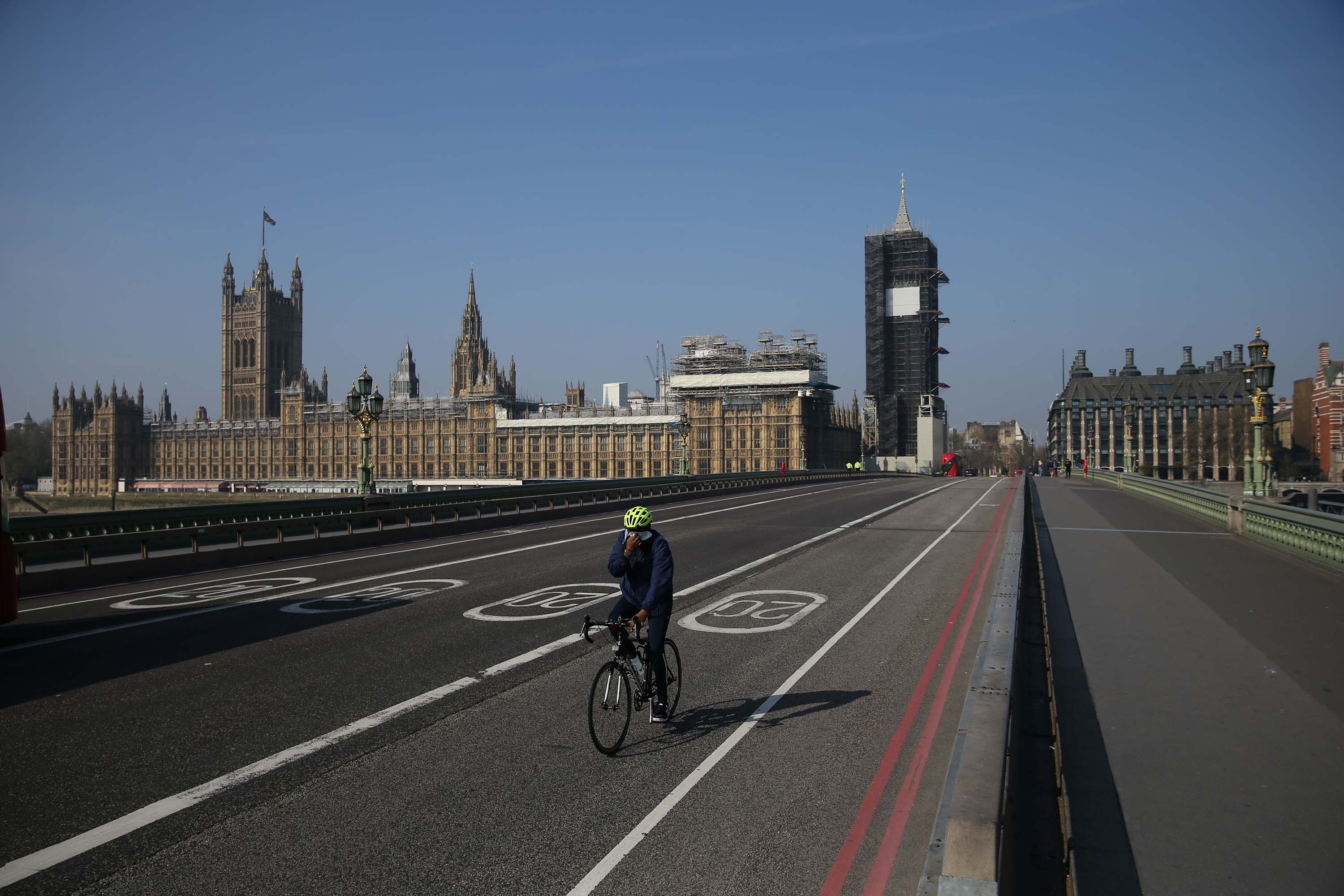 The UK Houses of Parliament are pictured as a cyclist crosses Westminster Bridge in London, England, on April 9.
