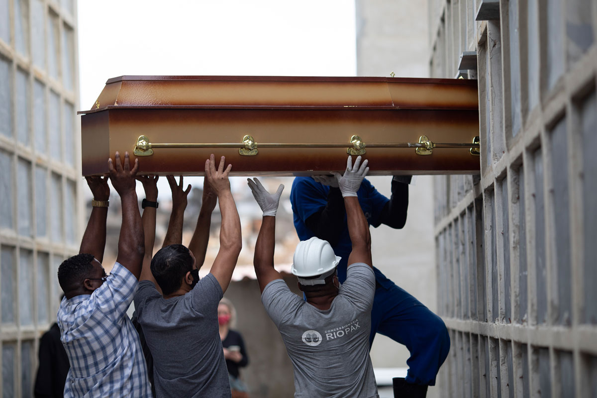 The remains of a woman who died from complications related to Covid-19 are placed into a niche by cemetery workers and relatives at the Inahuma cemetery in Rio de Janeiro, Brazil on April 13.