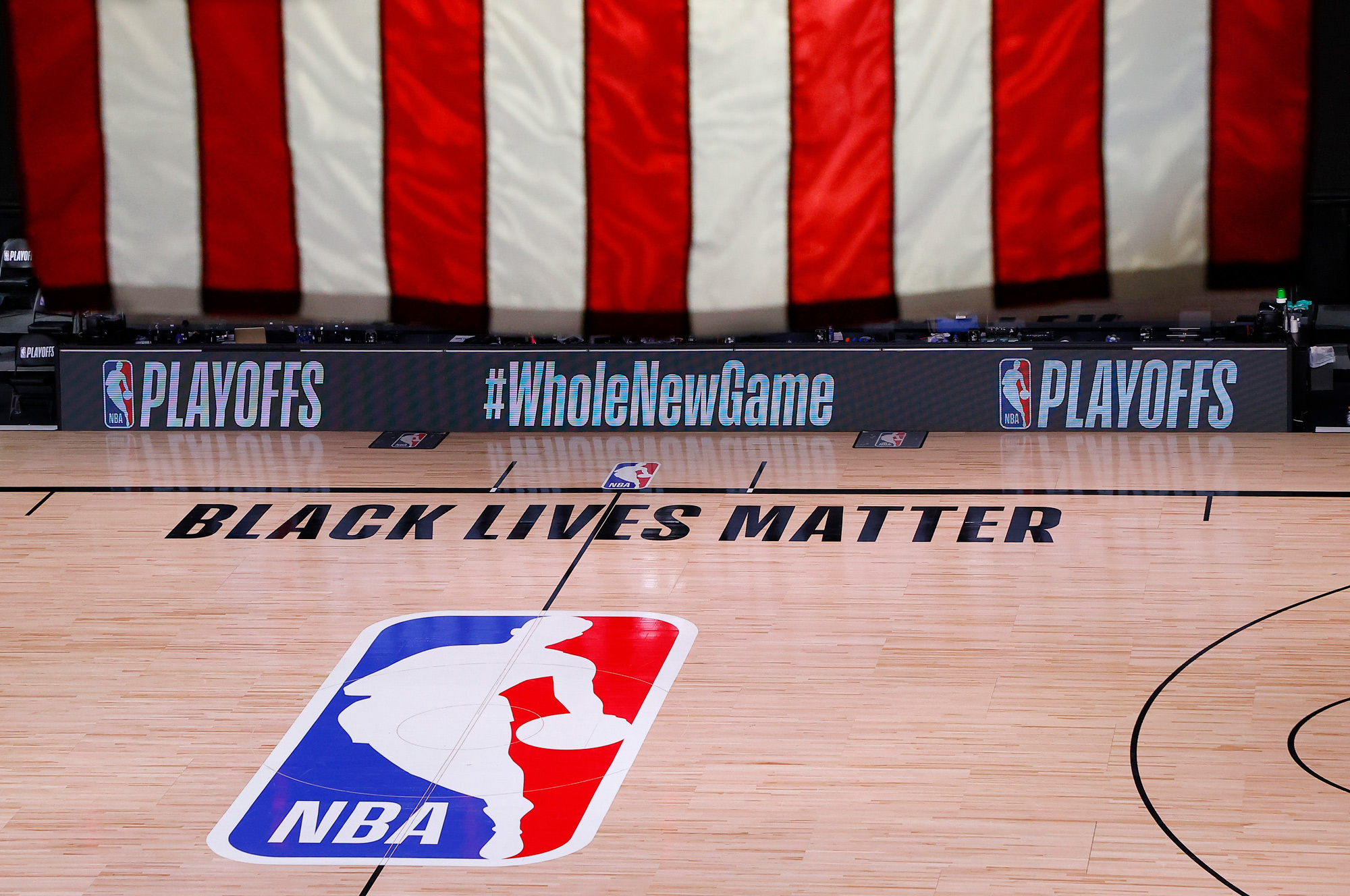 An empty court and bench are shown following the scheduled start time of Game 5 of an NBA basketball first-round playoff series on August 26 in Lake Buena Vista, Florida.