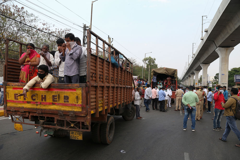 Migrants from Andhra Pradesh state attempting to return to their native villages on foot are moved on trucks to a government facility during a lockdown in Hyderabad, India, on Tuesday, April 14.