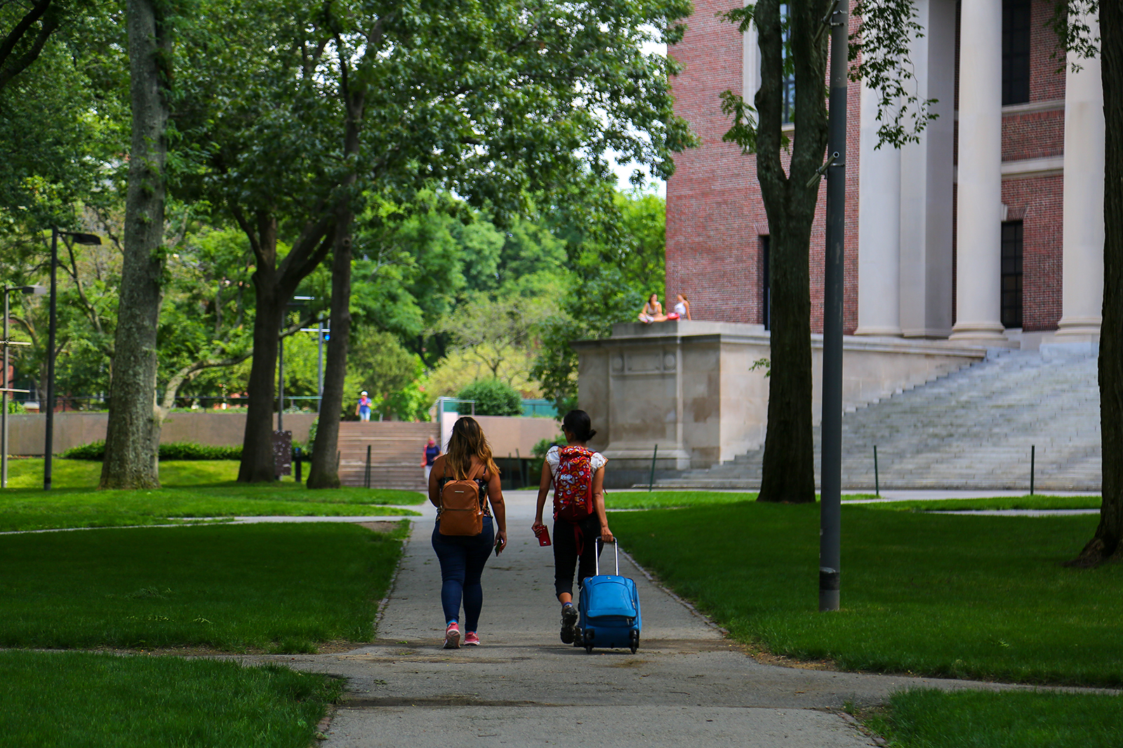 Two students are seen leaving their campus with baggage at Harvard University premises in Cambridge, Massachusetts on July 08.