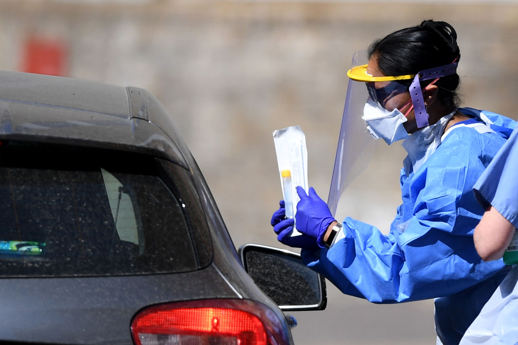 A medical worker speaks to a driver about a coronavirus test kit at a testing facility in London on April 25.