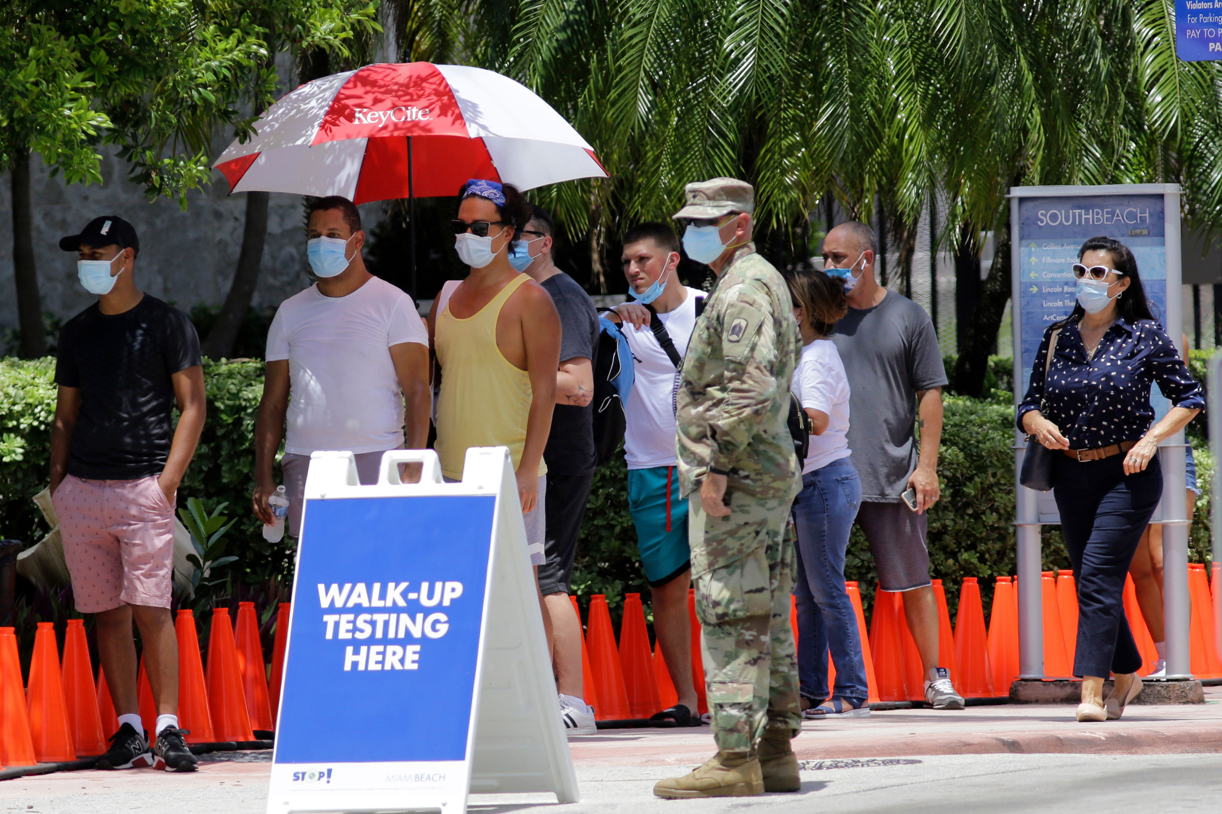 People wait in line at a walk-up testing site for COVID-19 during the new coronavirus pandemic, Tuesday, June 30, 2020, in Miami Beach, Flao