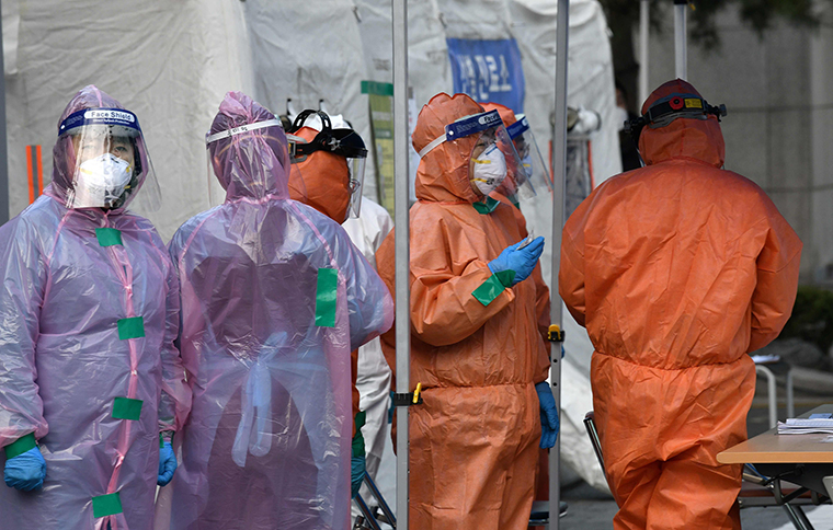 Medical staff members wait for people with suspected symptoms of the novel coronavirus, at a testing facility in Seoul on Wednesday, March 4.