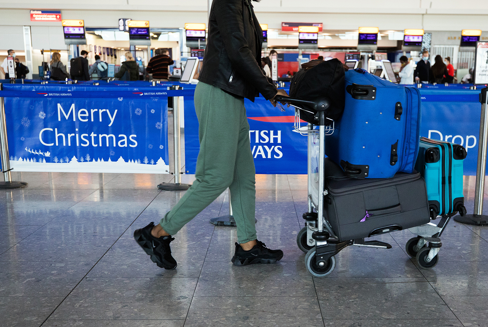 A passenger passes a 'Merry Christmas' sign in the check-in area at London Heathrow Airport in London, on December 19.