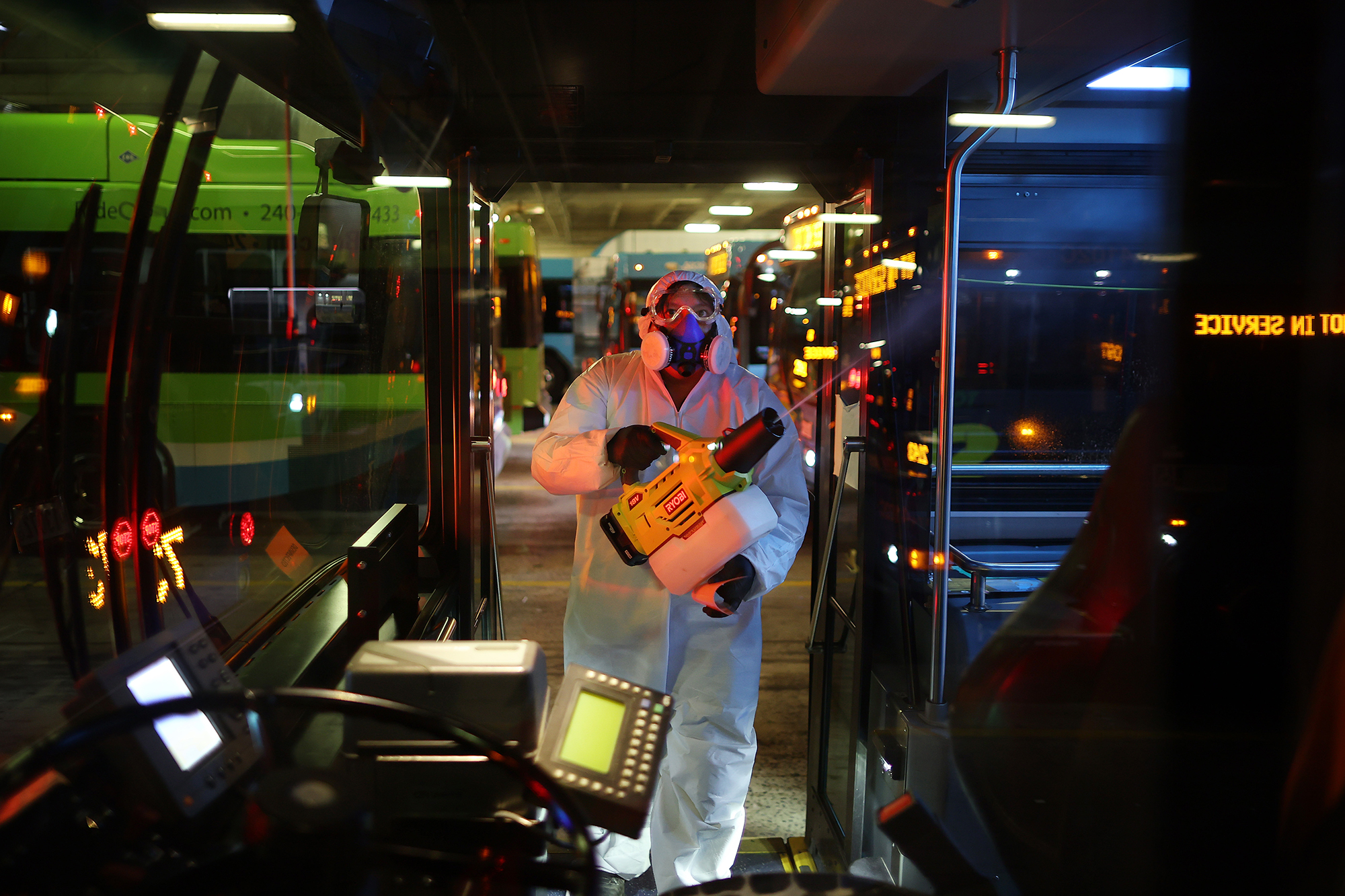 A worker disinfects public buses at the Montgomery County Division of Fleet Management Equipment Maintenance and Transit Operation Center March 20 in Rockville, Maryland.