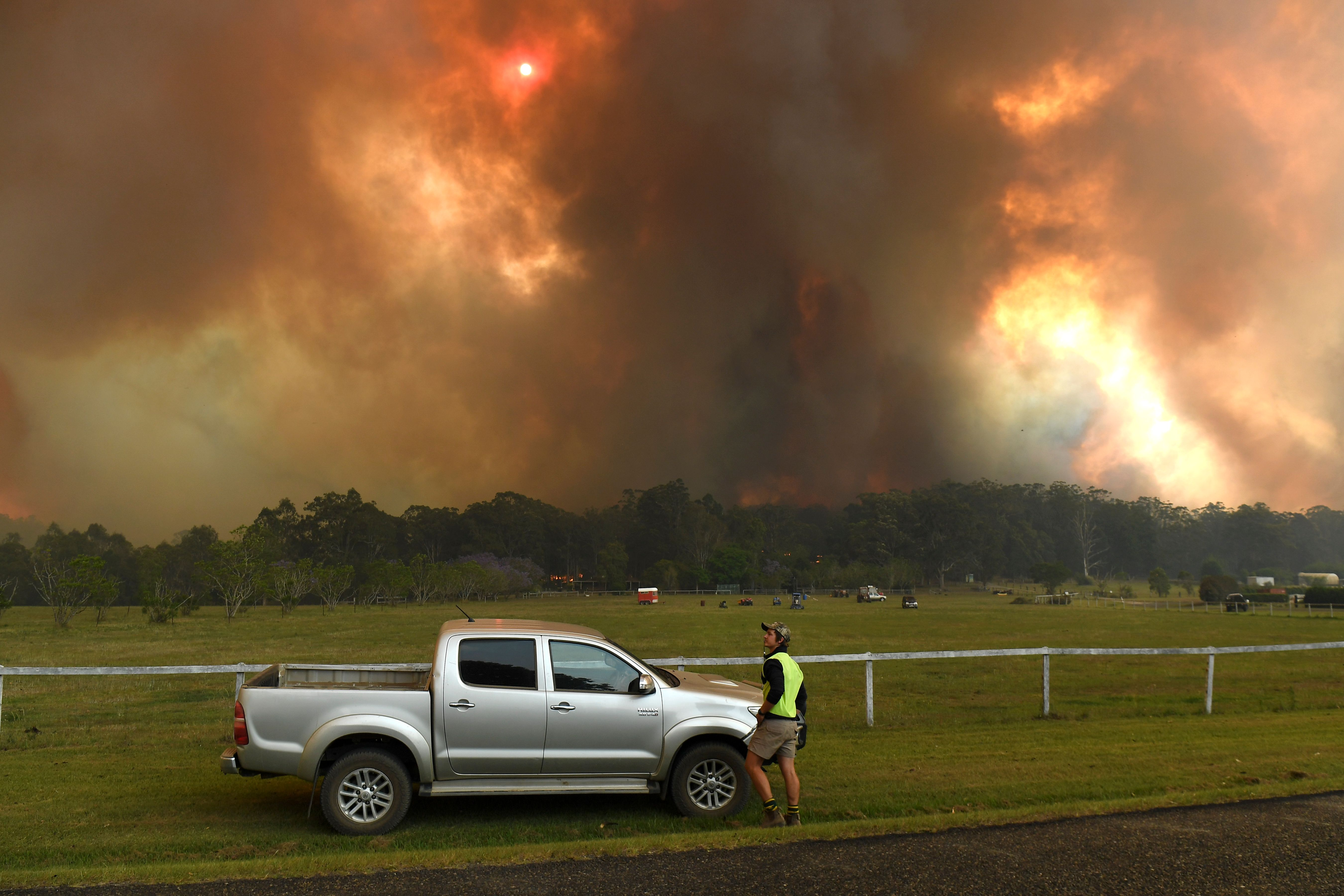 Locals watch fires near farmland in the regional center of Nana Glen, about 600 kilometers (372 miles) north of Sydney, on November 12.