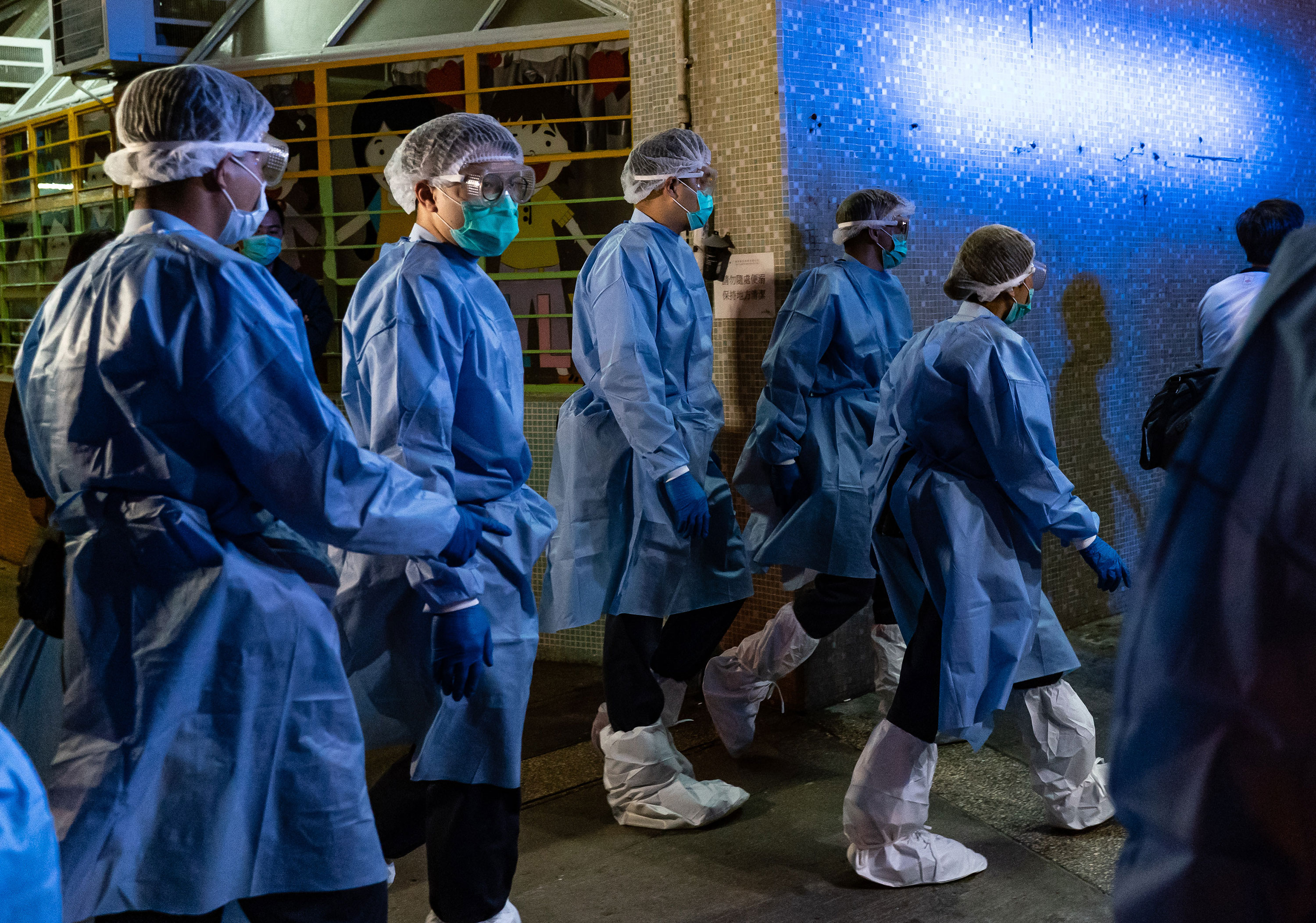 Police arrive at a public housing building as residents are evacuated from their home to a quarantine center after multiple infections of the novel coronavirus at Fu Heng Estate on March 14 in Hong Kong.