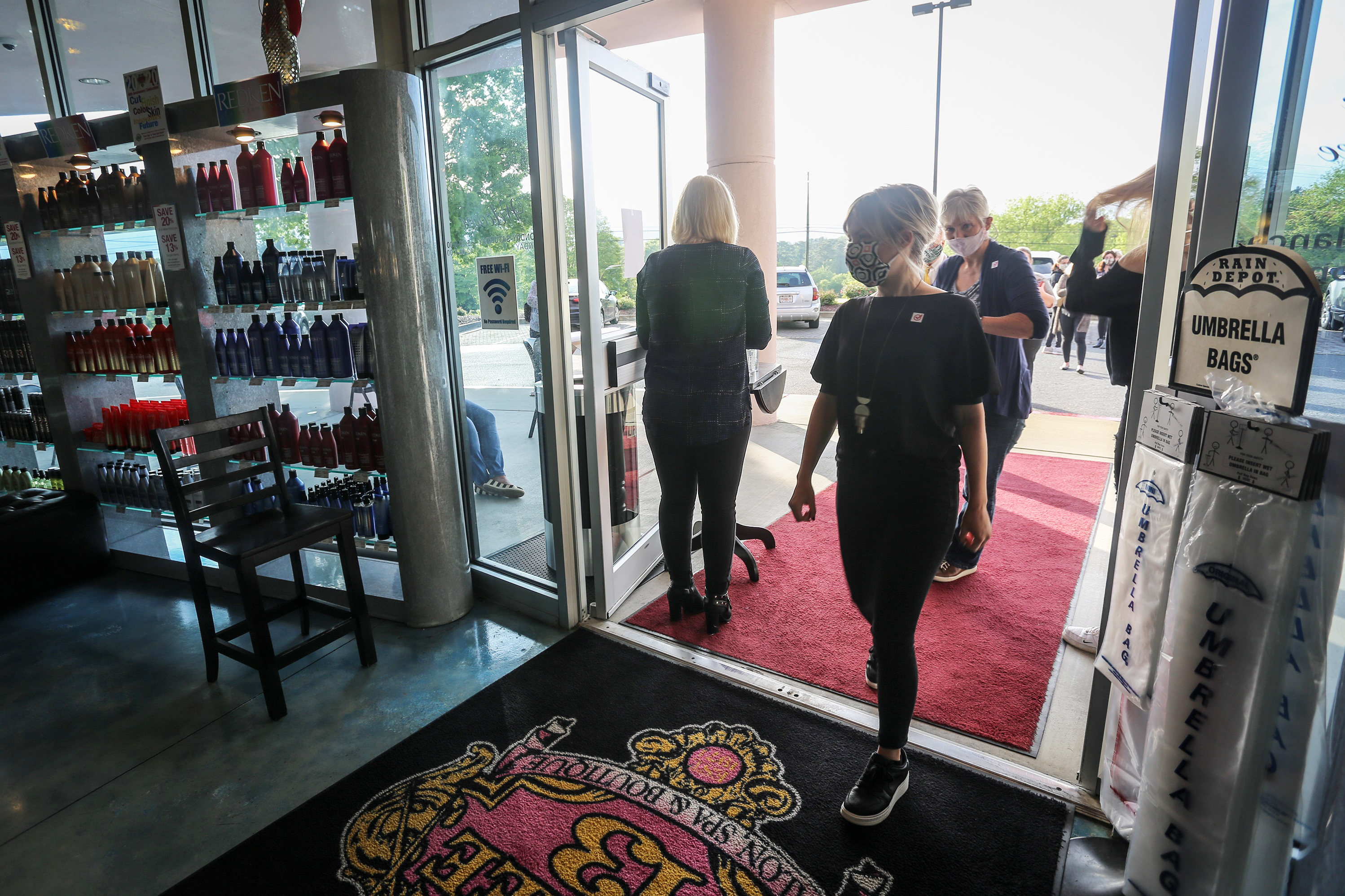 Employees and customers walk into Three-13 Salon, Spa & Boutique in Marietta, Georgia, on April 24. The salon reopened on April 24 after having been closed for more than a month due to the novel coronavirus outbreak.