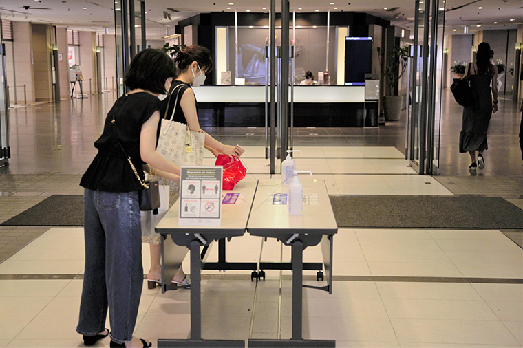 People wearing face masks wash their hands with hand sanitizer at an entrance of a shopping mall on July 11, in Tokyo.