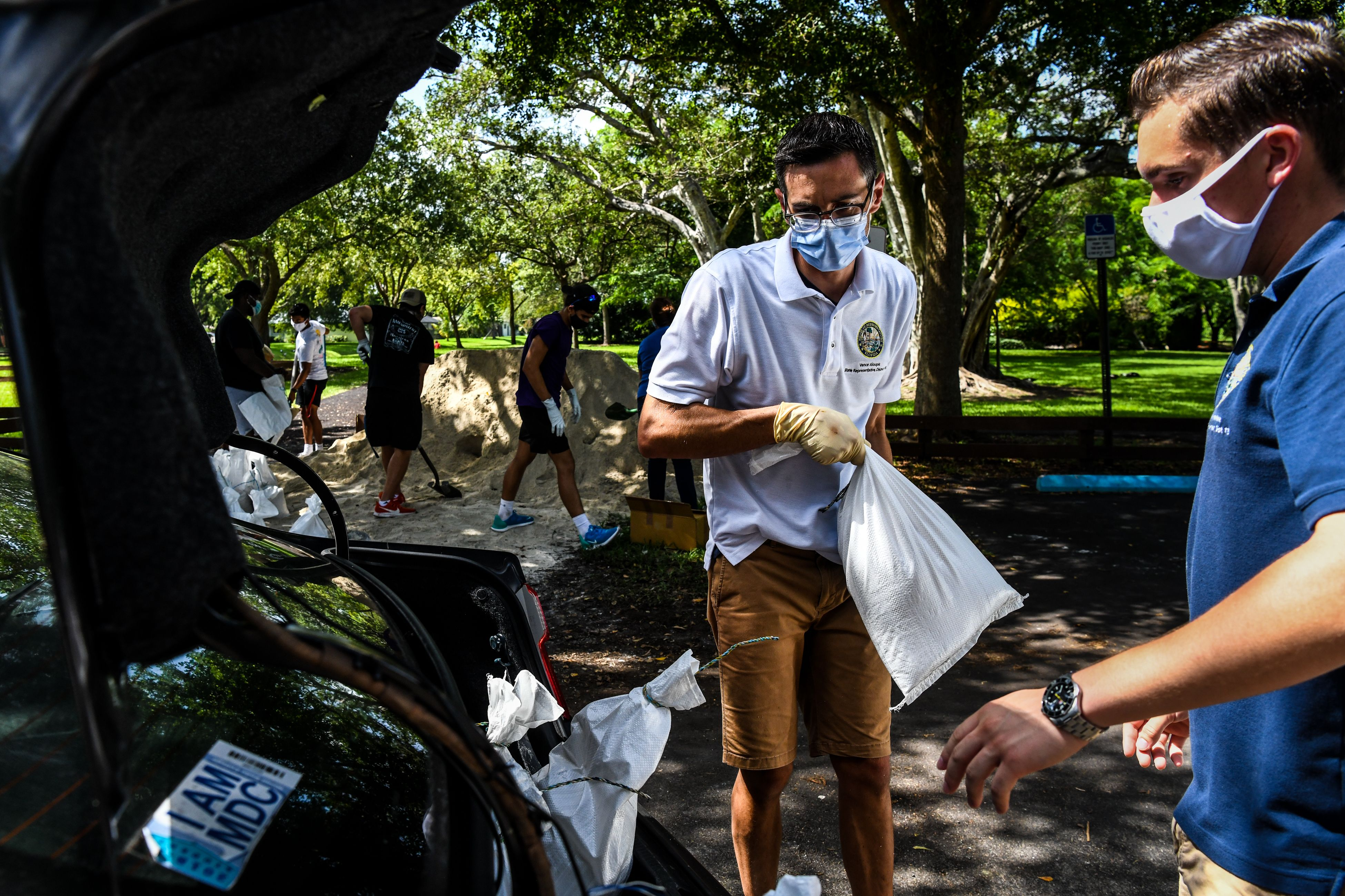Member of Florida House of Representatives Vance Aloupis (center) puts sand bags in a resident's car trunk in Palmetto Bay near Miami, on Friday as Floridians prepare for Hurricane Isaias.