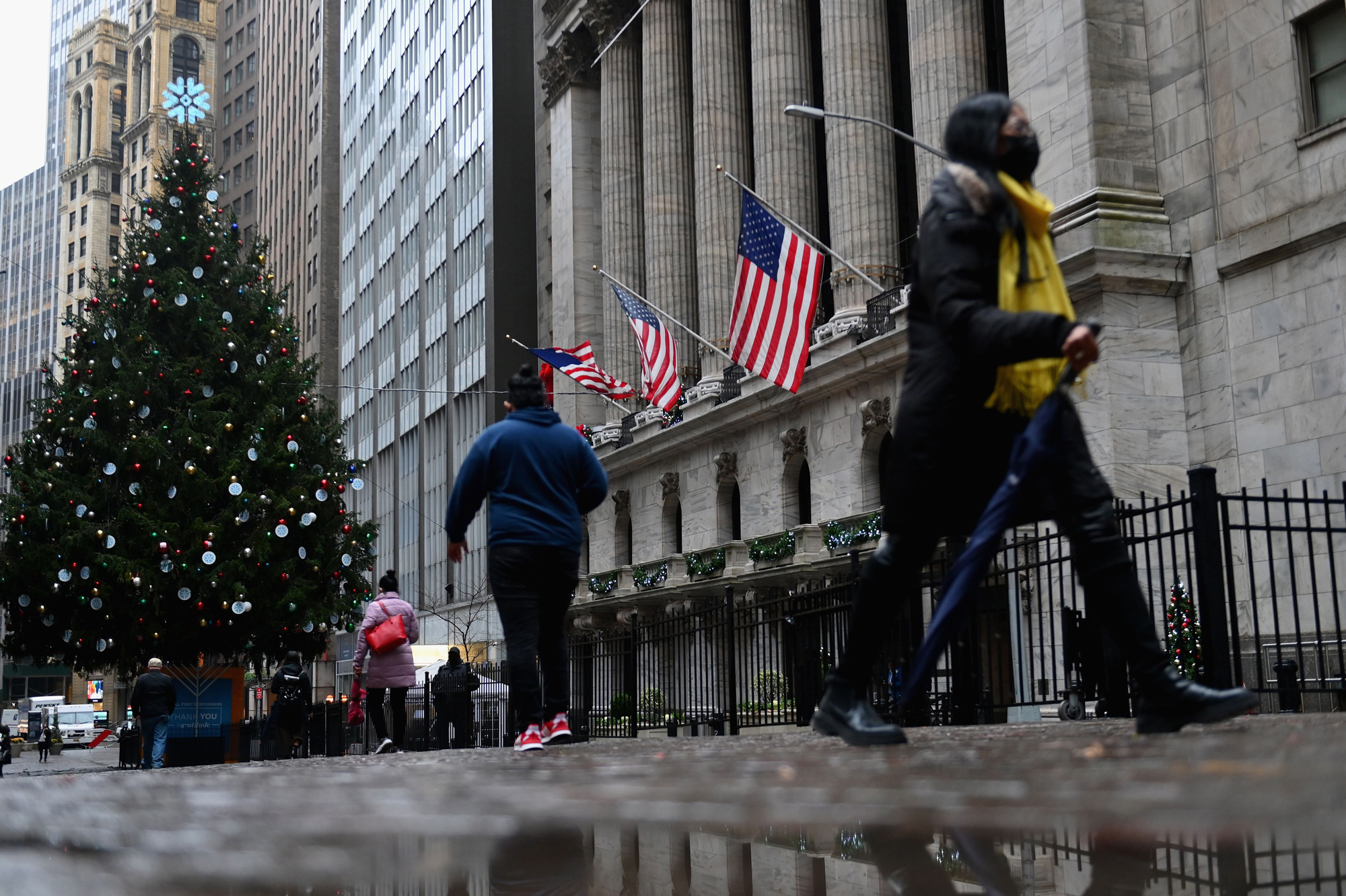 People walk past the New York Stock exchange at Wall Street on November 30 in New York City.
