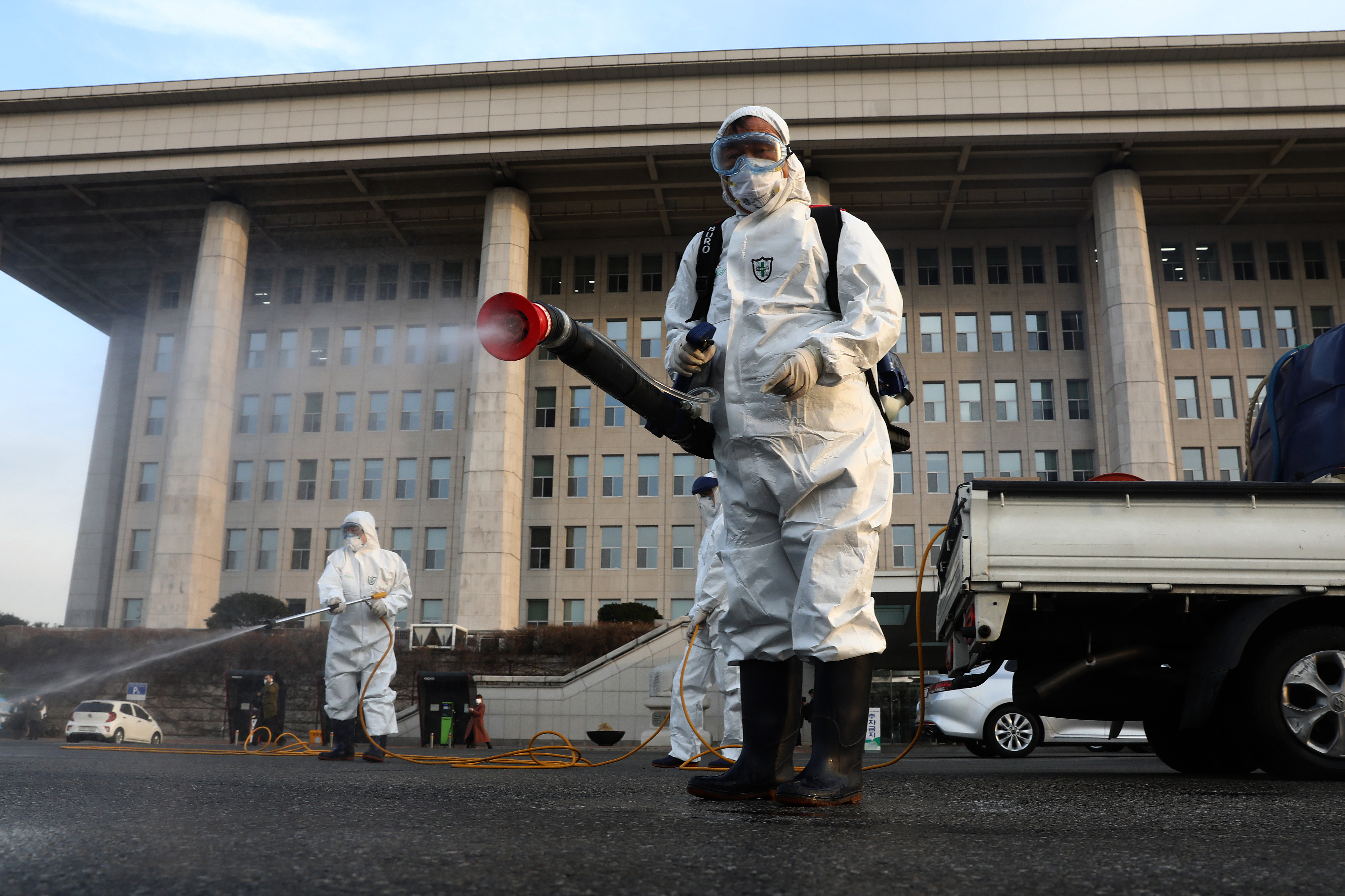 Disinfection professionals spray anti-septic solution outside the National Assembly building in Seoul.