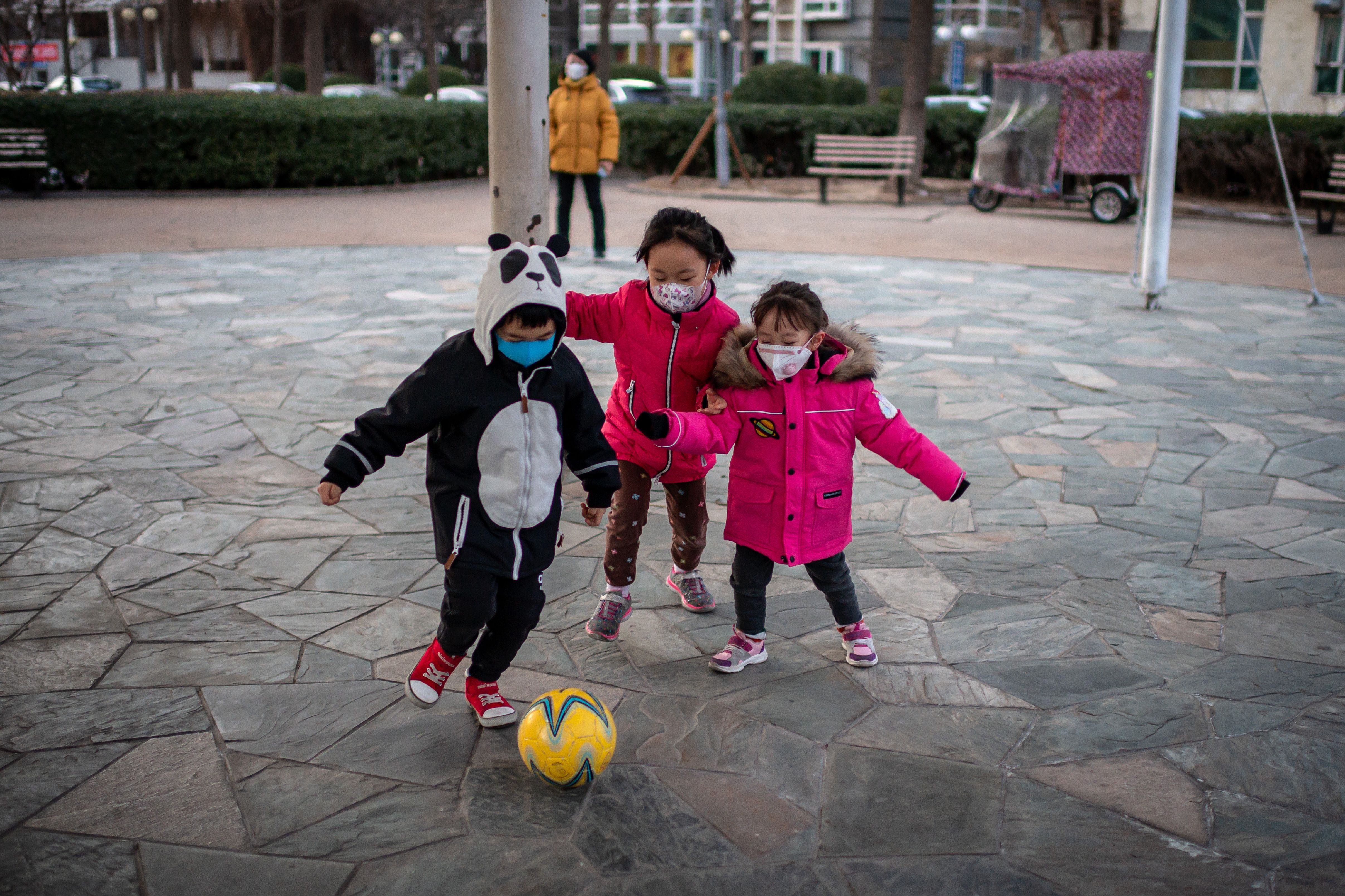 Children wearing protective facemasks to help stop the spread of the Wuhan coronavirus play soccer inside a condominium complex in Beijing.