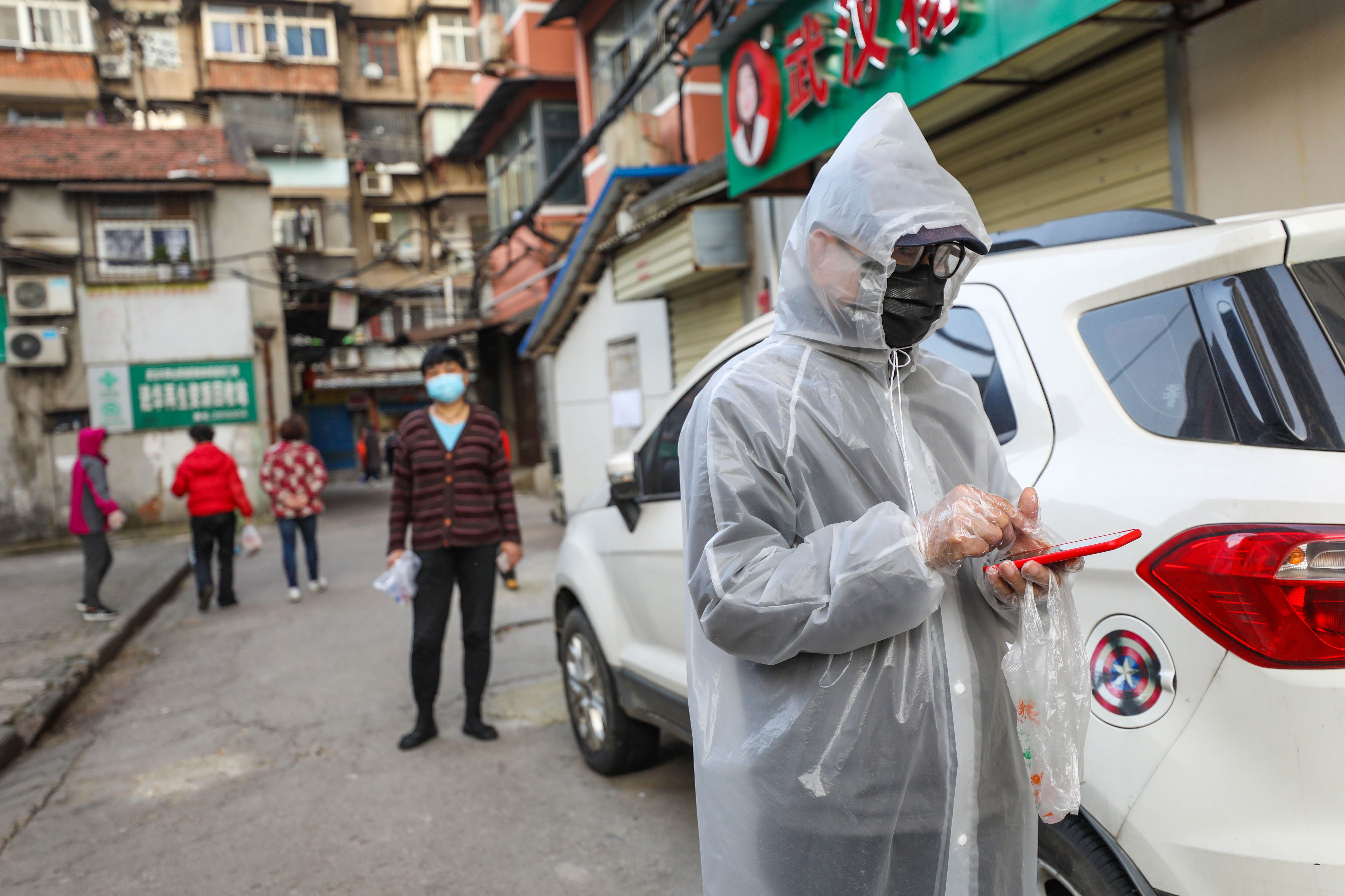 A resident dressed in a protective suit lines up with others to pick up pork which was delivered to their quarantined compound in Wuhan, in China's central Hubei province on March 18.