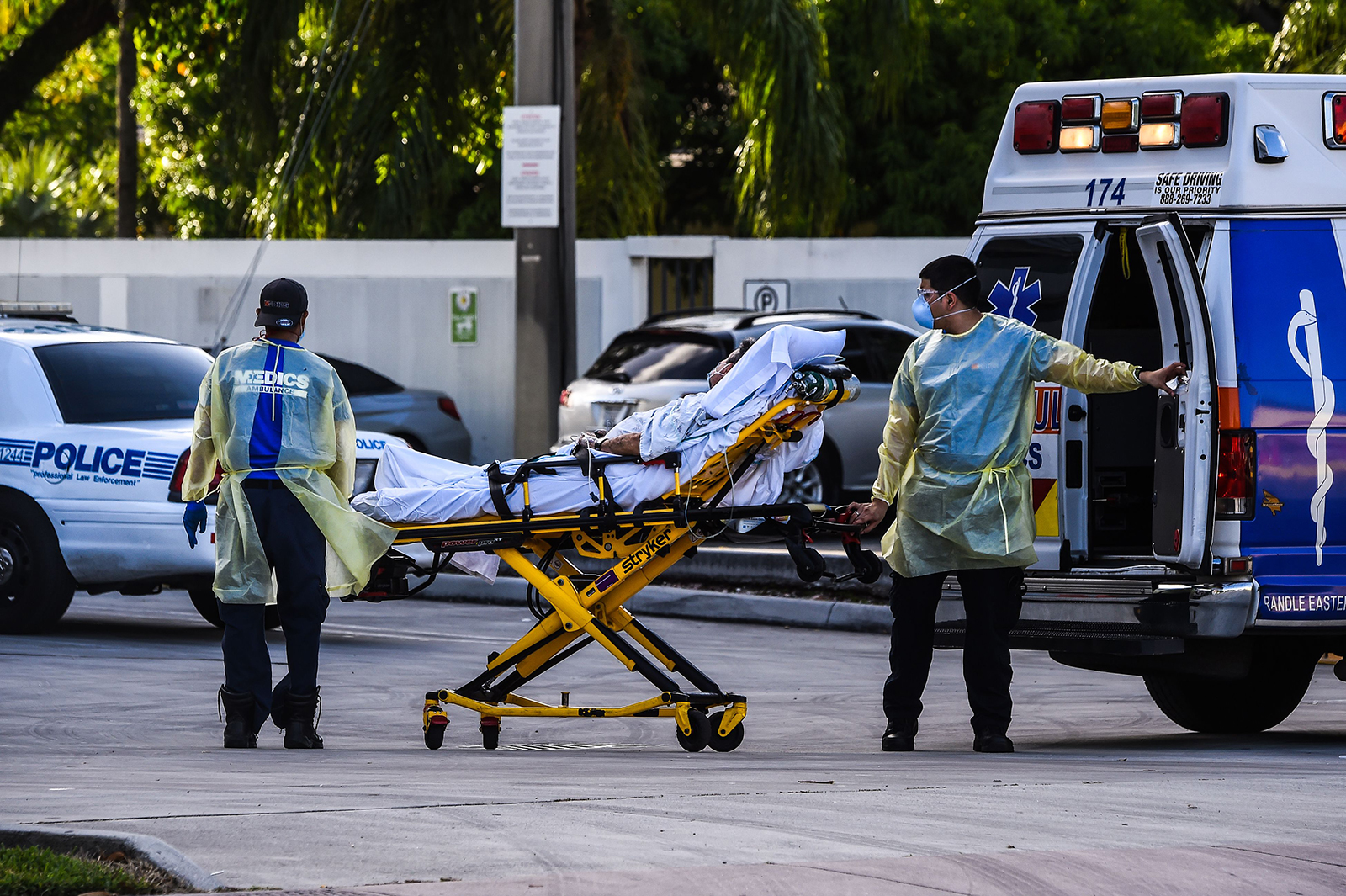 Medics transfer a patient on a stretcher from an ambulance outside Coral Gables Hospital near Miami on July 30.
