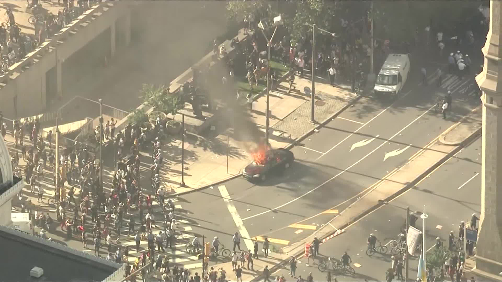 A vehicle fire burns in the street while protesters look on in Philadelphia, on May 30.