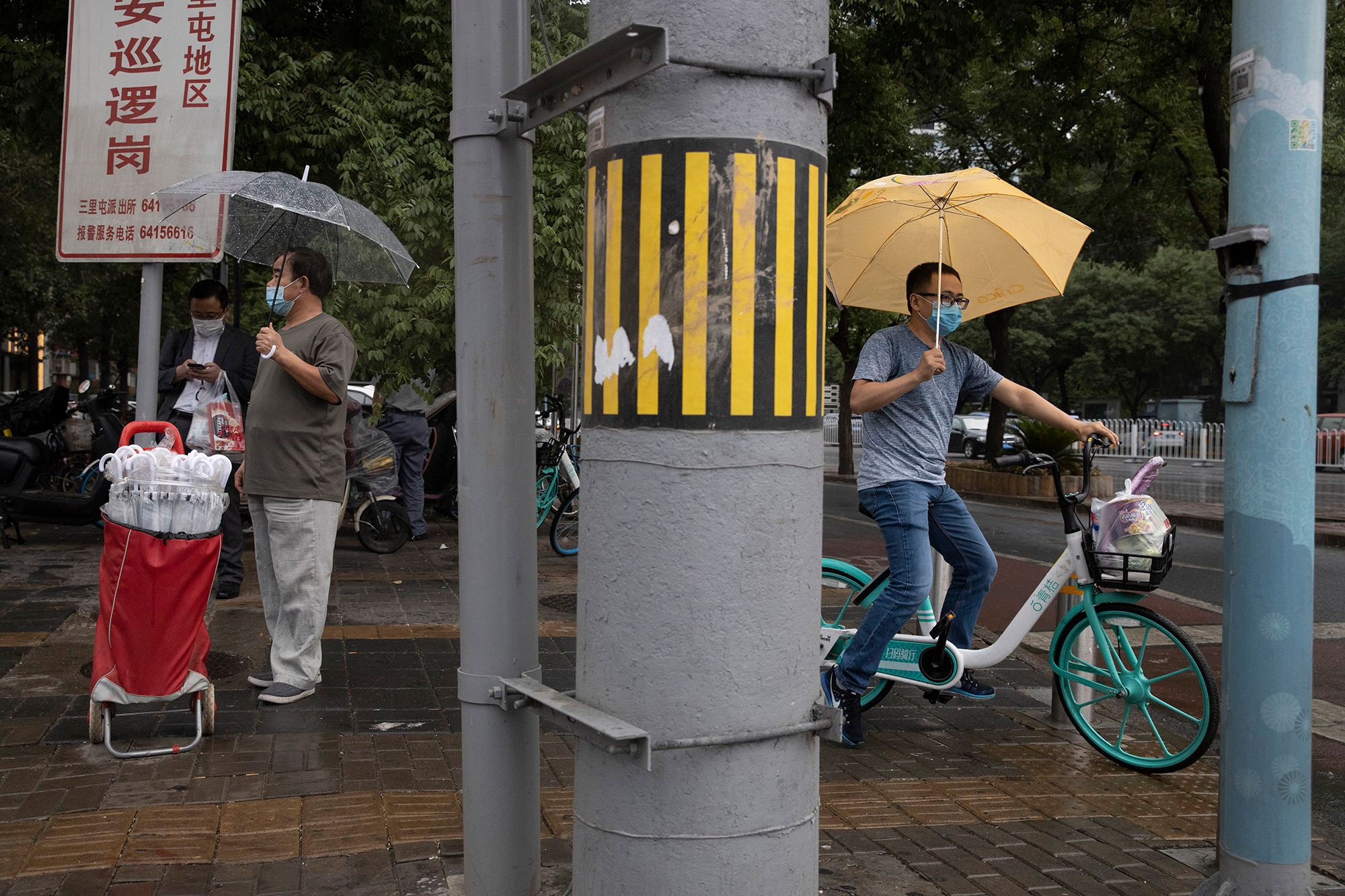 A man wearing a face mask to curb the spread of the coronavirus takes the opportunity to sell umbrellas as it rains in Beijing on Thursday, June 18, 2020.