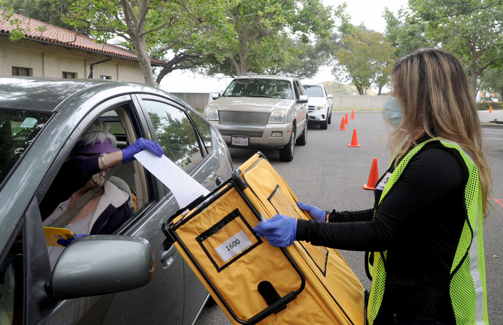 Kathie Webster, of Simi Valley, votes Tuesday from inside her car as Jessica Ocegueda, a records technician for the Ventura County Elections Office, helps with the special election for the 25th Congressional District at the polling station at the Ronald Reagan Presidential Library & Museum.