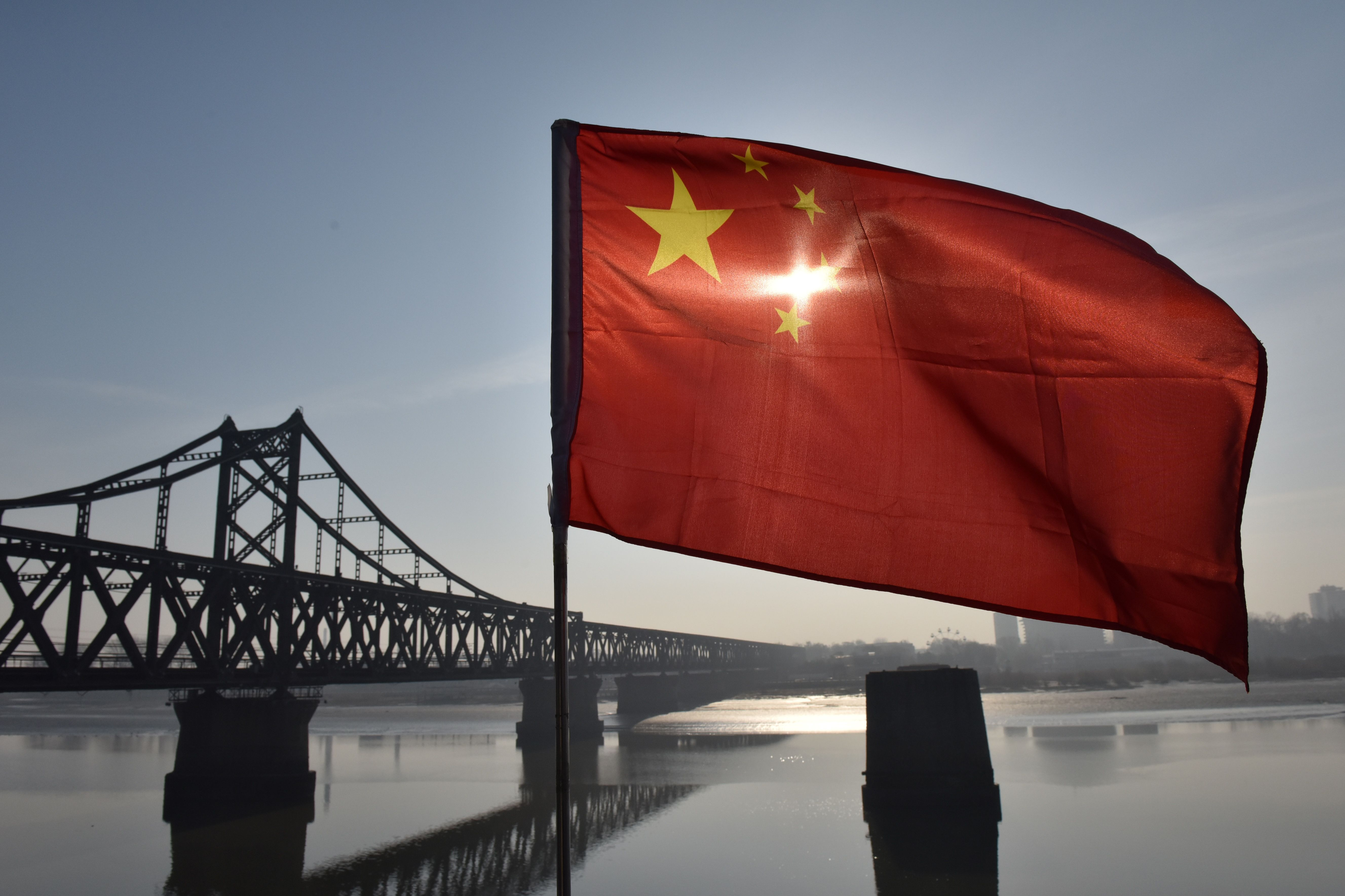 The Chinese flag flies on the Yalu River Broken Bridge, with the Sino-Korean Friendship Bridge, and the North Korean city of Sinuiju behind it, in the Chinese city of Dandong on February 23, 2019.