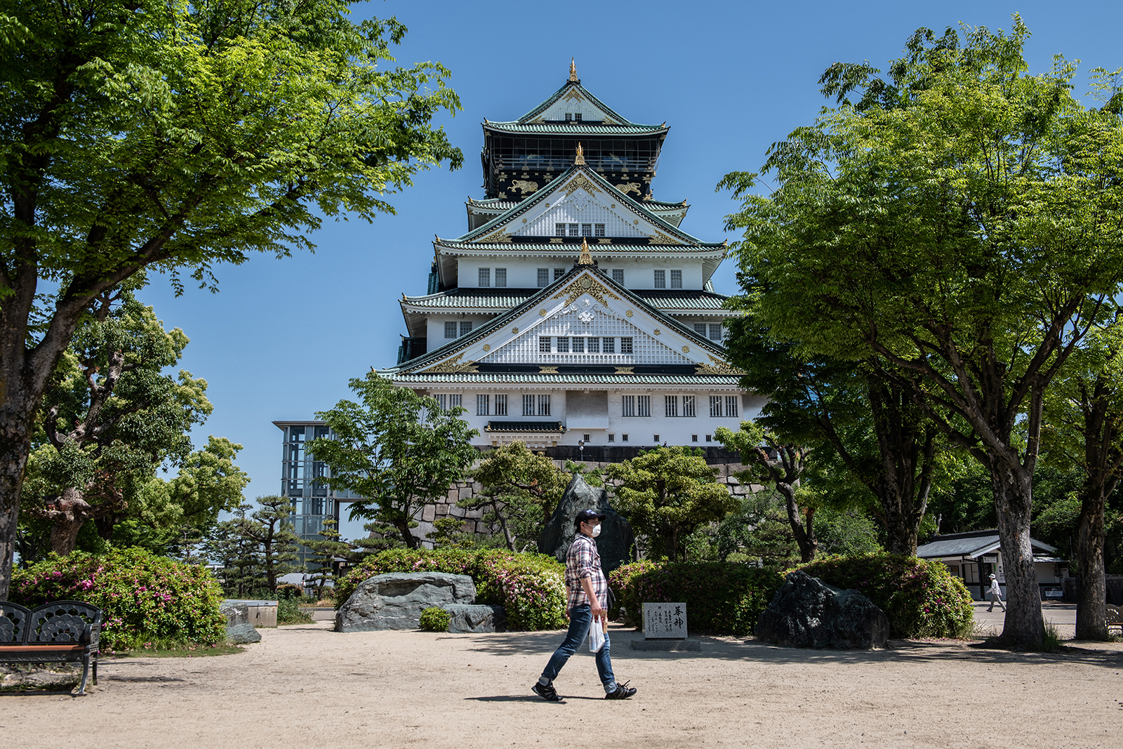 A man wearing a face mask walks in the grounds of Osaka Castle on May 14, in Osaka, Japan.