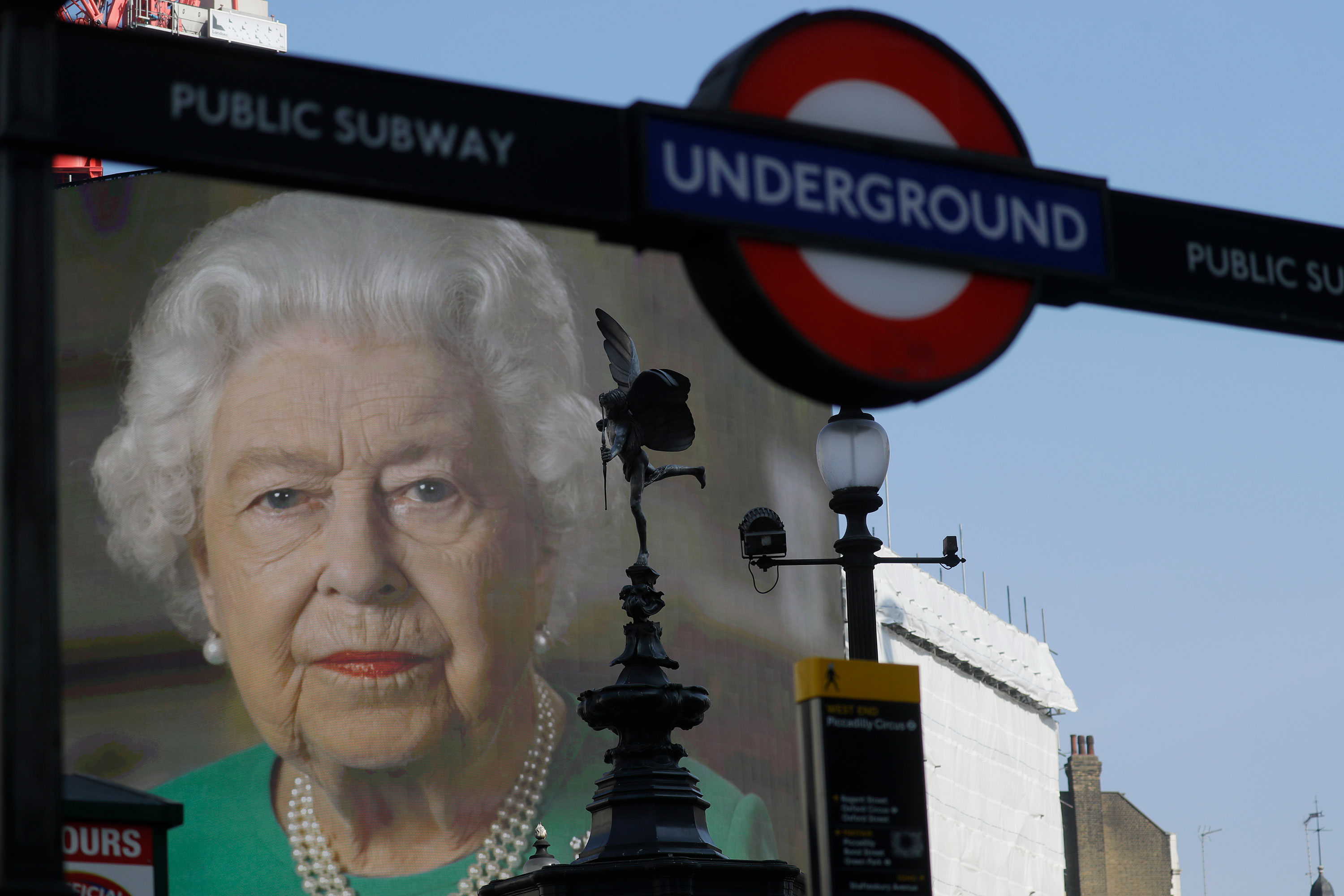 An image of Britain's Queen Elizabeth II and quotes from her historic television broadcast commenting on the coronavirus pandemic are displayed on a big screen behind the Eros statue and a London underground train station entrance at Piccadilly Circus in London on April 9.