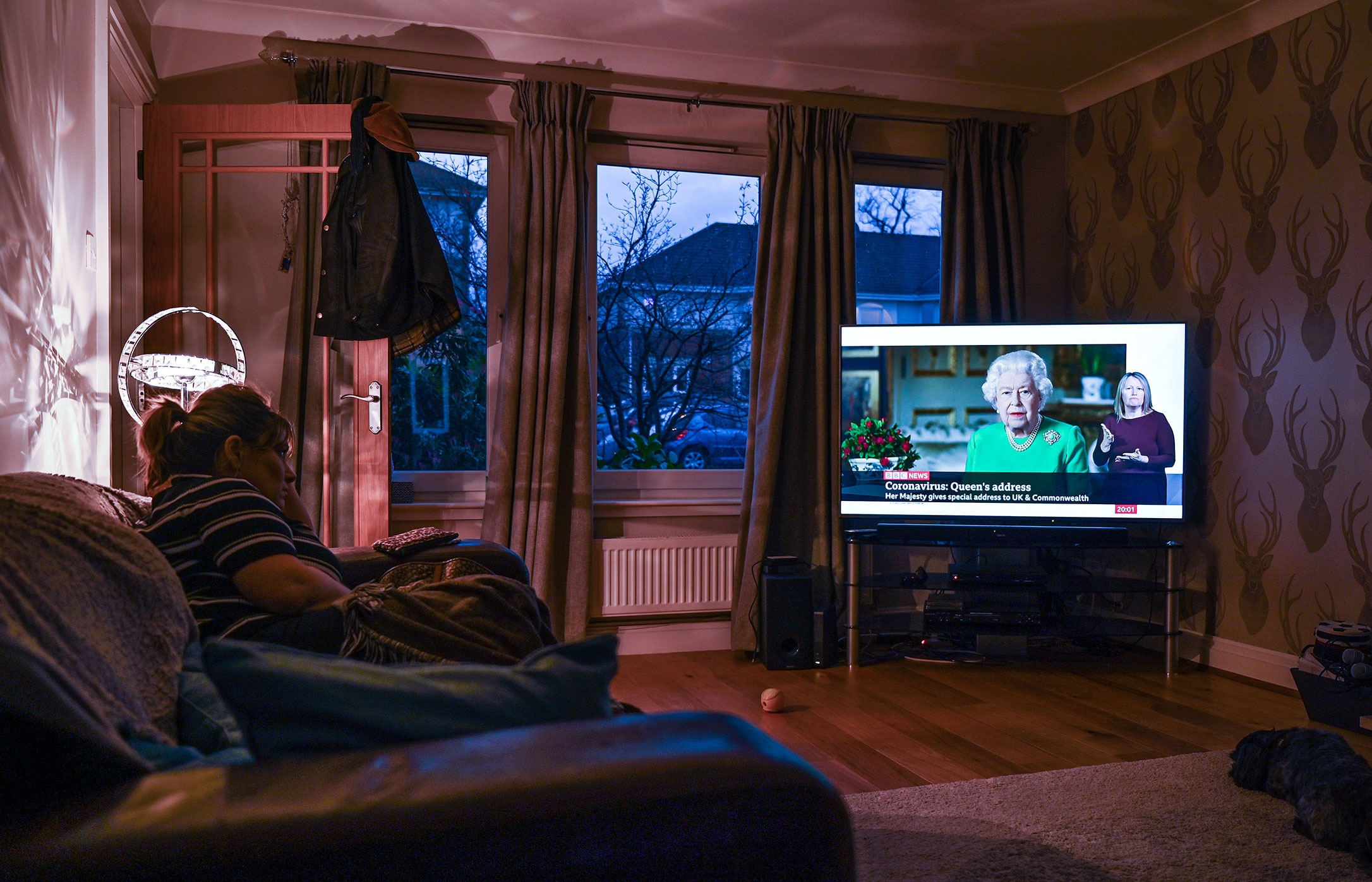 A woman watches Queen Elizabeth II's televised address to the nation on April 5, in Glasgow, Scotland.