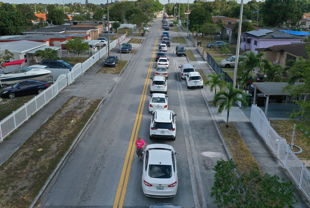 An aerial view from a drone shows vehicles lining up to receive unemployment applications being given out by City of Hialeah employees in front of the John F. Kennedy Library on April 8, in Hialeah, Florida.