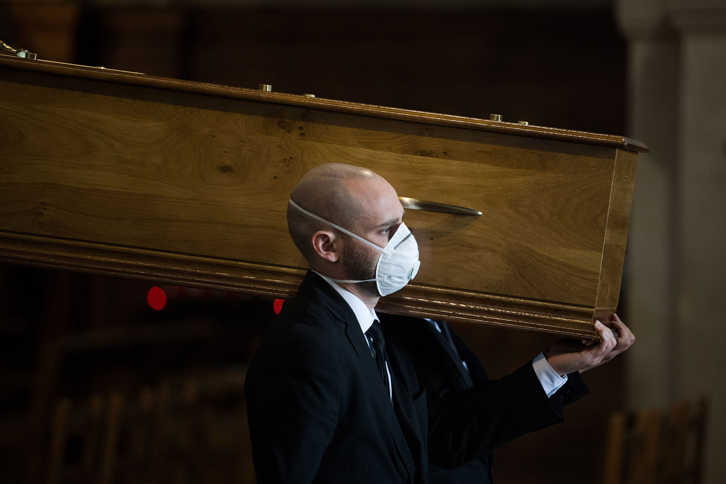 A pall bearer helps carry the coffin of a coronavirus victim through Saint Francois Xavier church at a funeral service in Paris, France, on April 16.