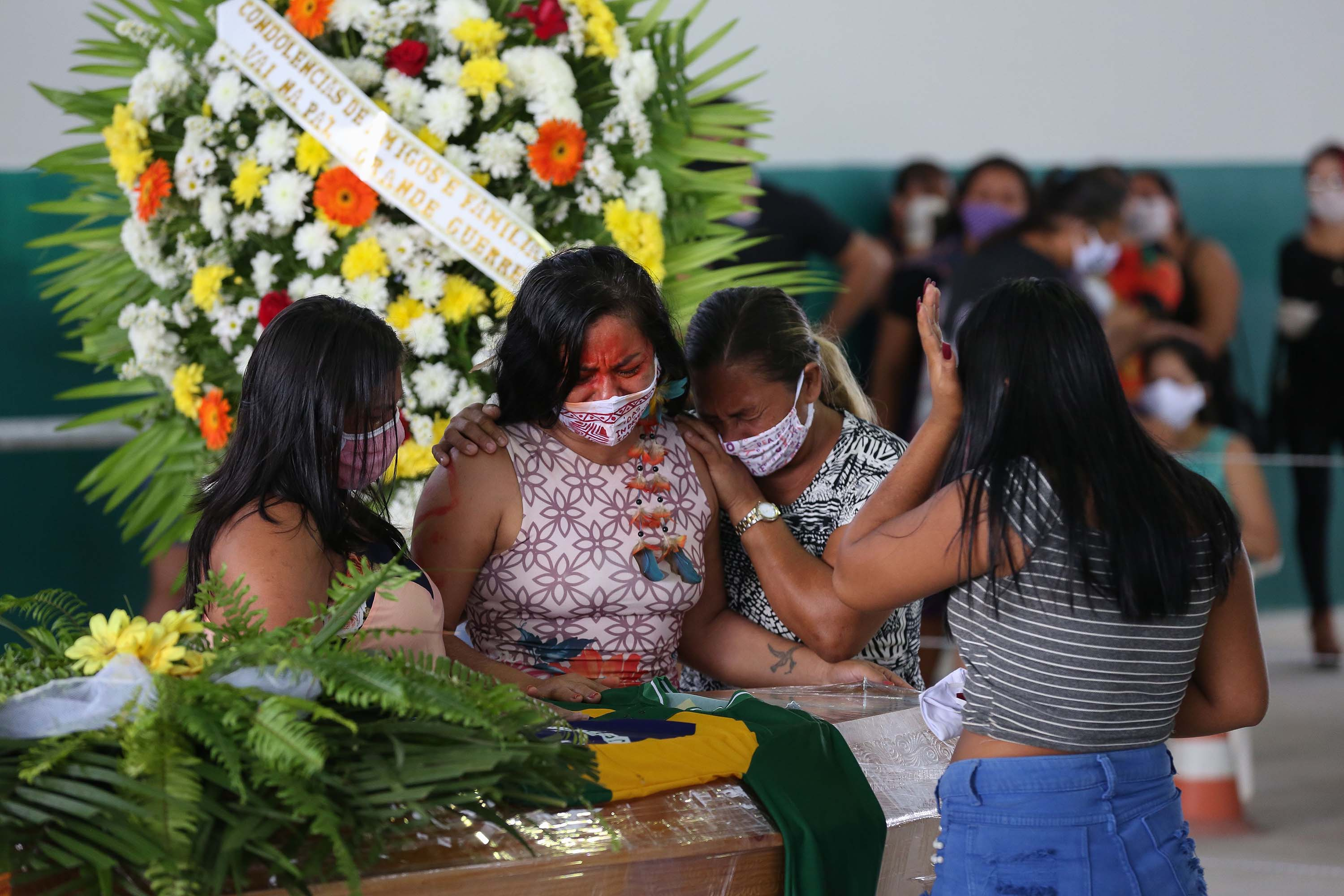 Members of the Parque das Tribos community mourn beside the coffin of Chief Messias, 53, of the Kokama tribe, who died from coronavirus, in Manaus, Brazil, on May 14.