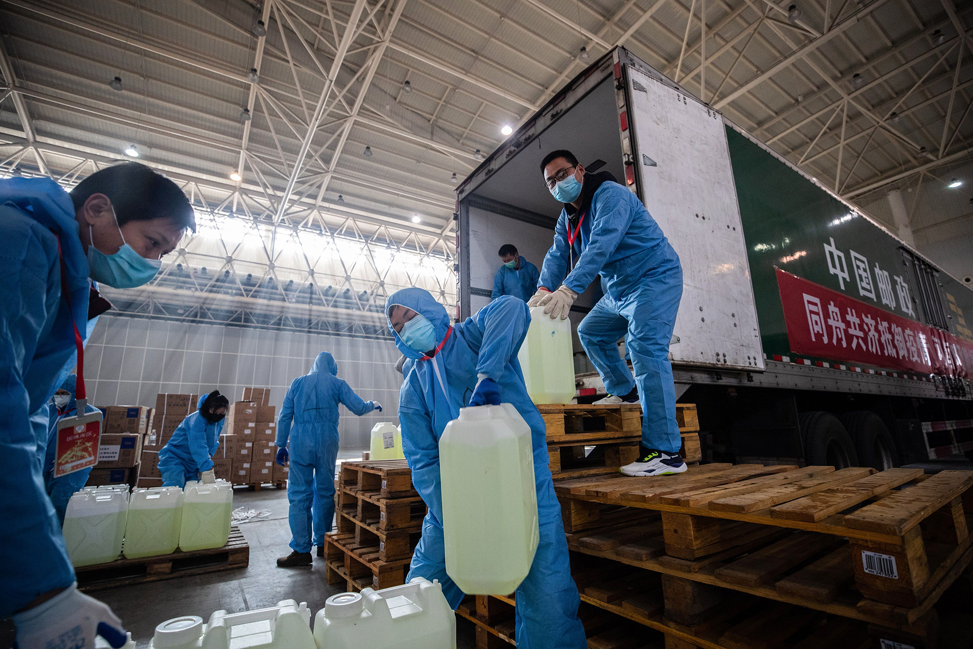 Staff members and and volunteers wearing protective face masks transfer medical supplies at a warehouse converted into a makeshift hospital in Wuhan on February 4.