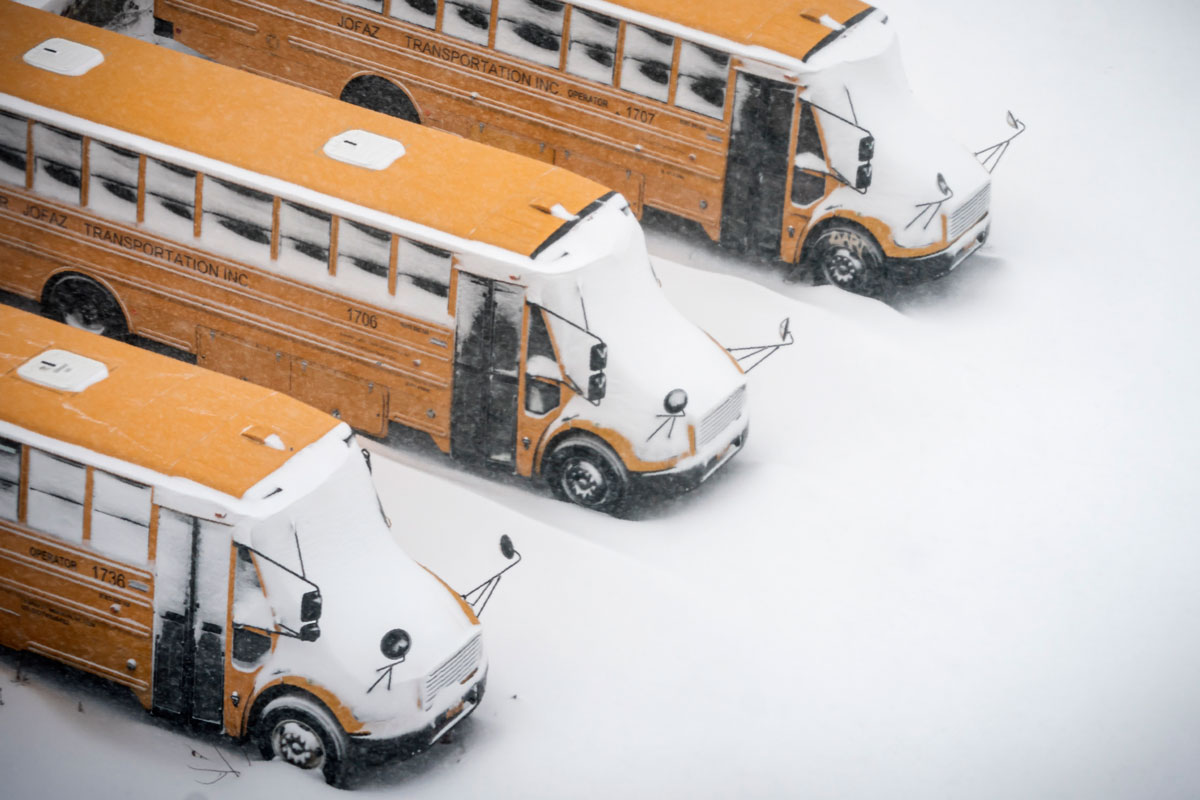 School buses are covered in snow during a snowstorm on February 1 in Brooklyn, New York.