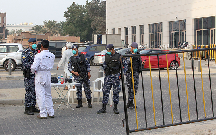 Members of Kuwait's national guard wear safety masks as they keep watch outside a hotel in the capital where Kuwaitis returning from Iran are quarantined and tested for the virus, on Monday, February 24.