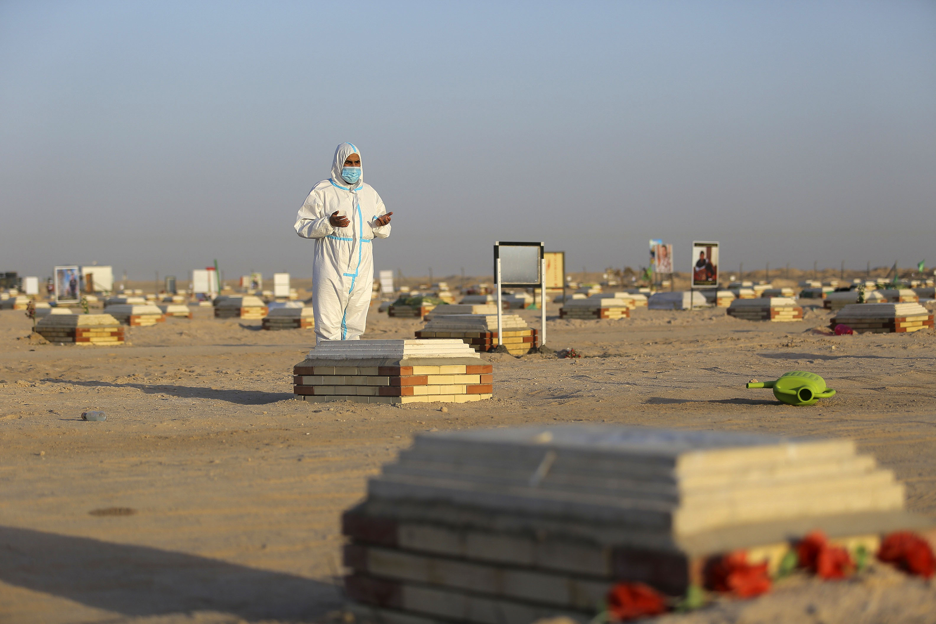 A person prays by the grave of someone said to have died from Covid-19 at a cemetery near Najaf, Iraq, on July 20.