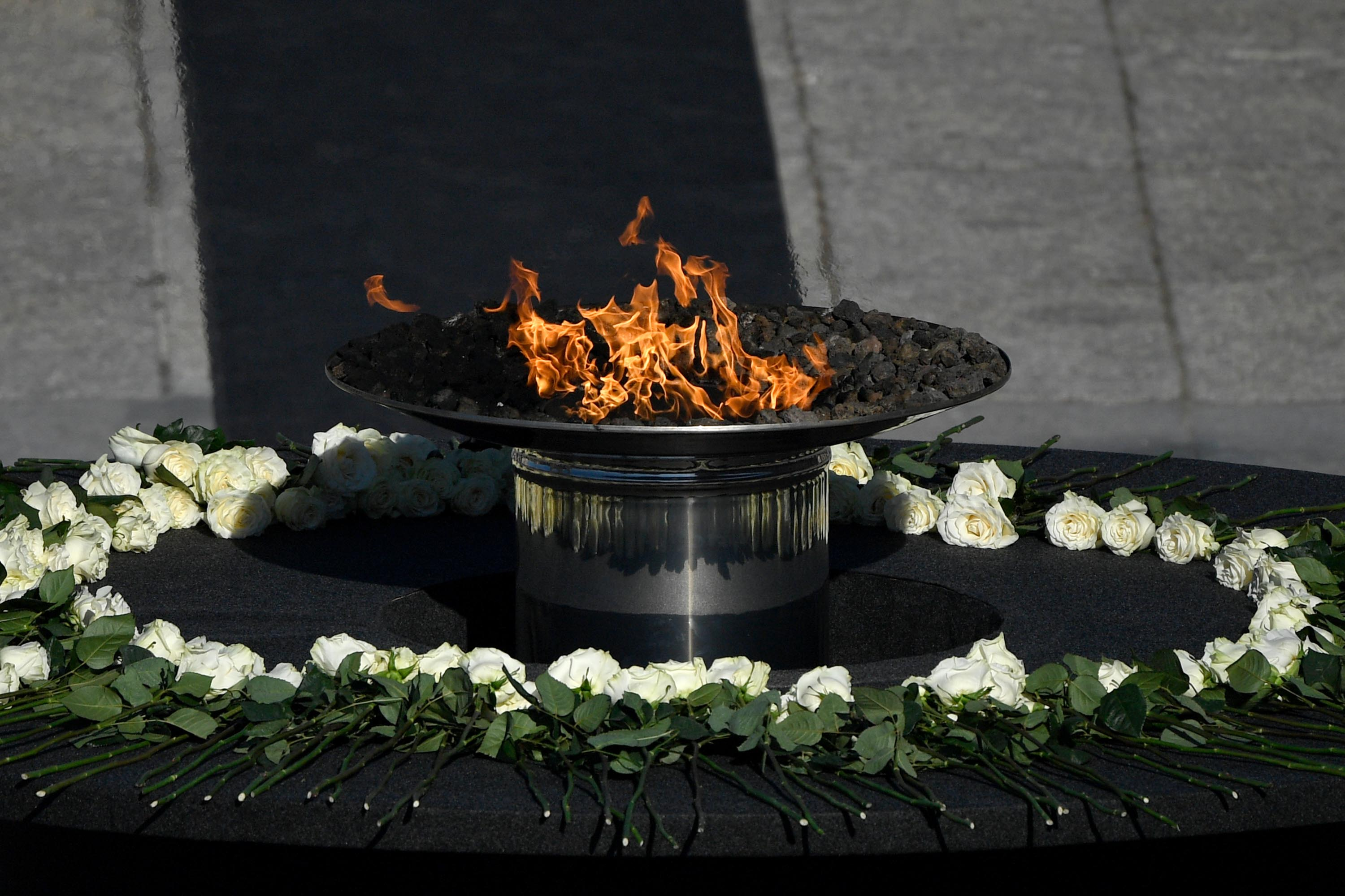 A flame burns on a cauldron surrounded by white roses during a state ceremony to honor Spanish victims of the coronavirus crisis, as well as public servants, at the Royal Palace in Madrid, on Thursday, July 16.