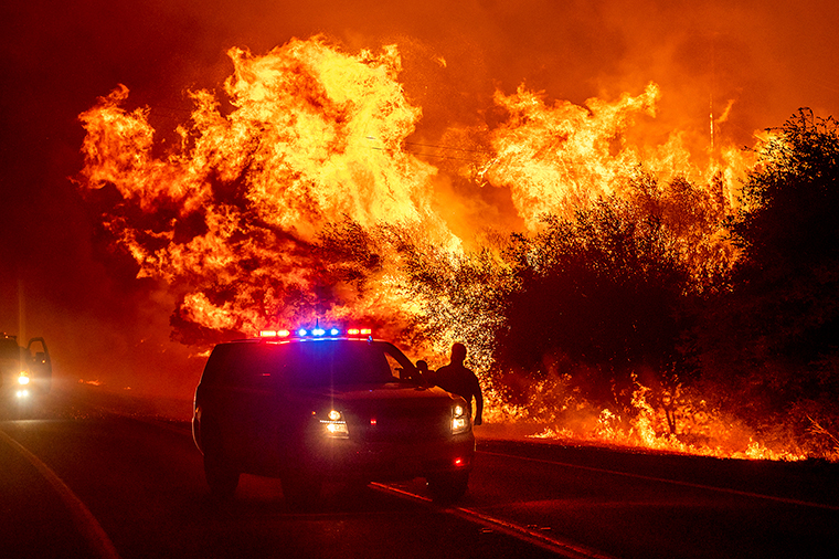 Flames lick above vehicles on Highway 162 as the Bear Fire burns in Oroville, California, on Wednesday, September 9. The blaze, part of the lightning-sparked North Complex, expanded at a critical rate of spread as winds buffeted the region.