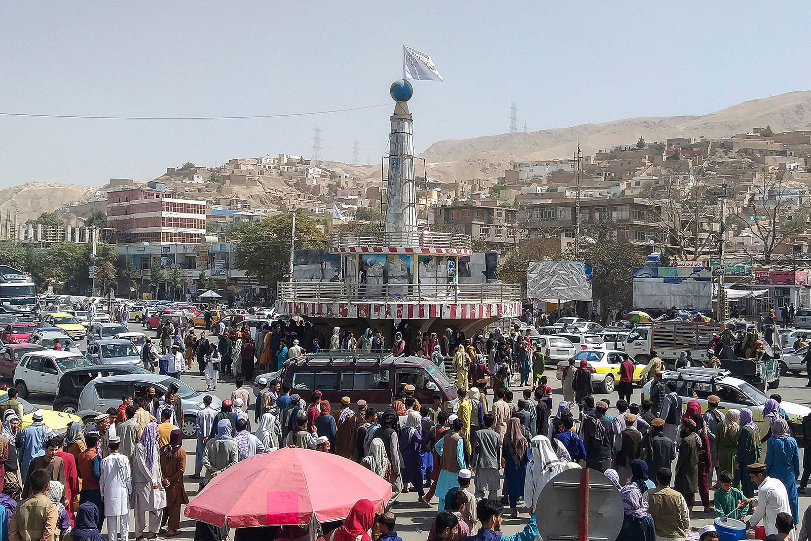 A Taliban flag is seen on a plinth with people gathered around the main city square at Pul-e-Khumri on August 11.